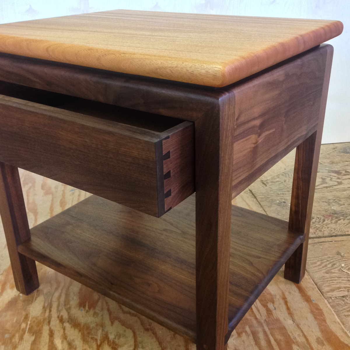 Side table featuring a floating mahogany top with a push thru walnut drawer and lower shelf.