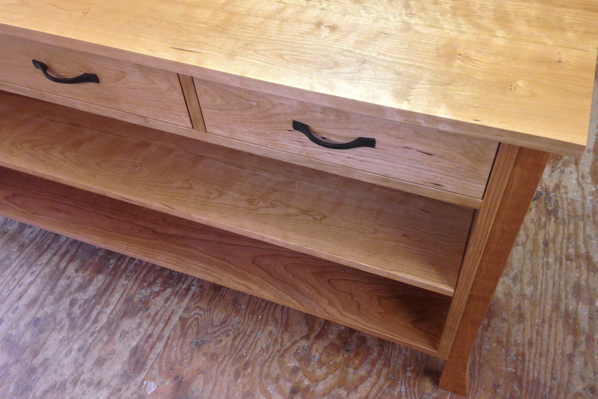 A sideboard with three upper drawers and an adjustable lower shelf in an all cherry design.
