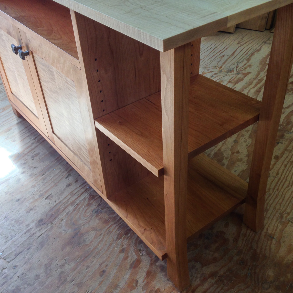 An adjustable shelf and open end on a cherry case with curly maple top and door panels.