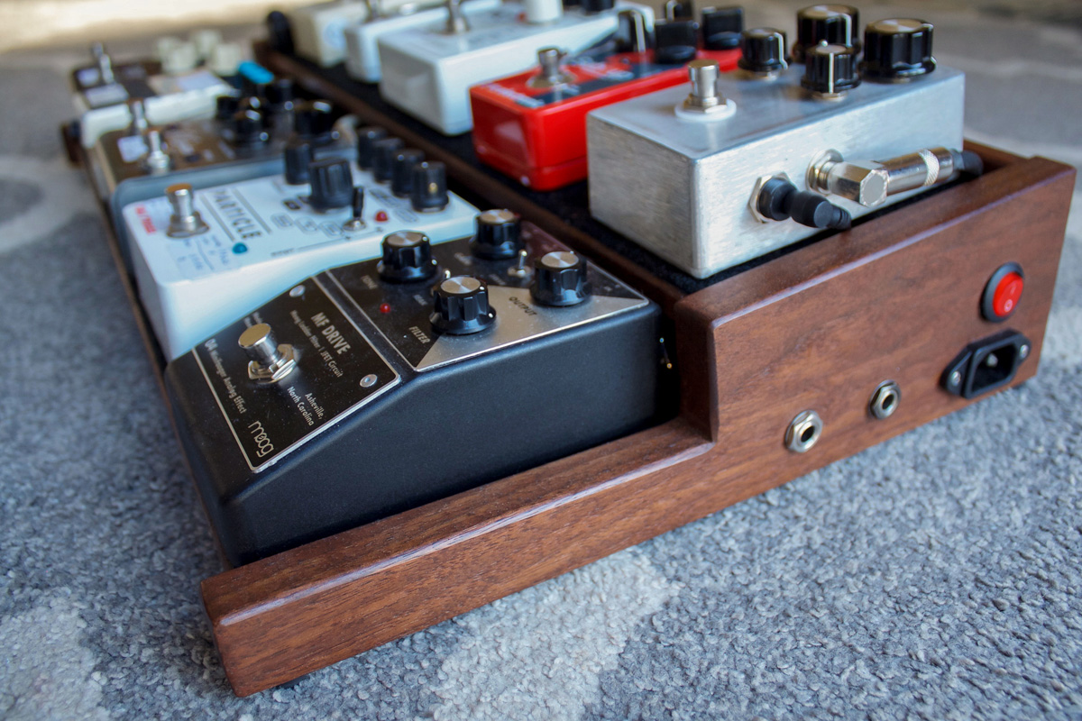 Custom walnut pedal board for guitar effects pedals. It is inspired by wooden end caps on vintage synthesizers and has an  underside mounted power supply and wired input/ouput jacks on one side panel.