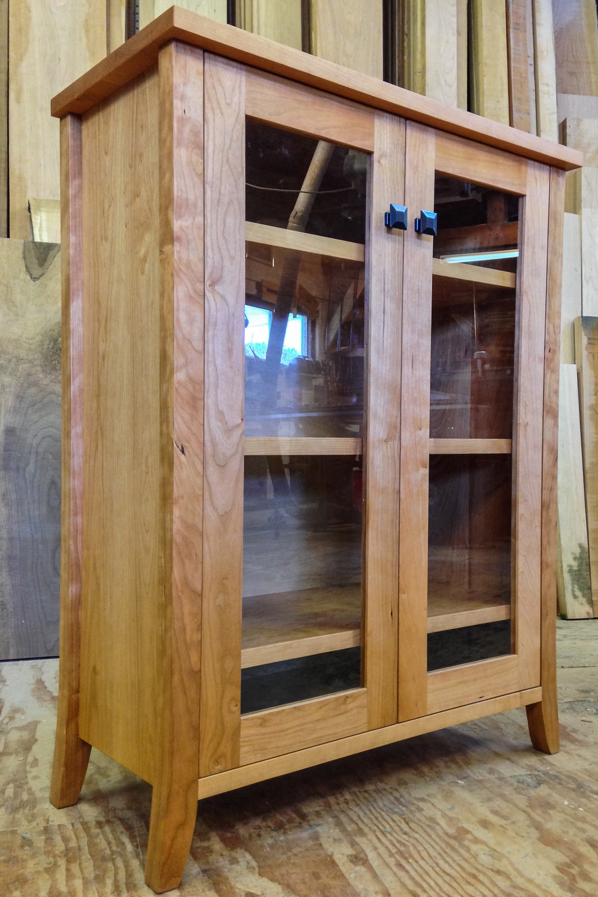 Custom cherry cabinet with adjustable shelves and glass doors.