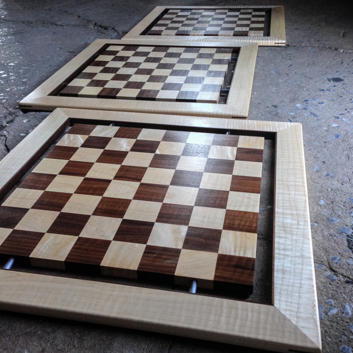 Curly maple and walnut floating chess boards. The boards are retained into a mitered and splined frame by four steel rods.