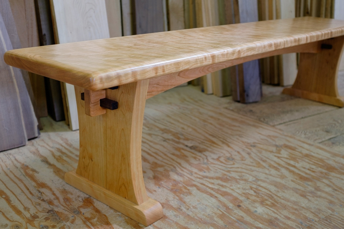 6.5 ft curly cherry bench top on a trestle base.