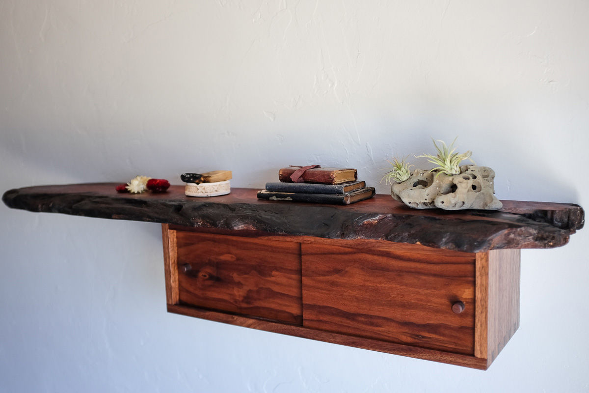 Salvaged redwood hanging shelf with dovetail walnut box featuring sliding pocket doors. The redwood live edge of the redwood tells of fire, I retained the blackened edge.