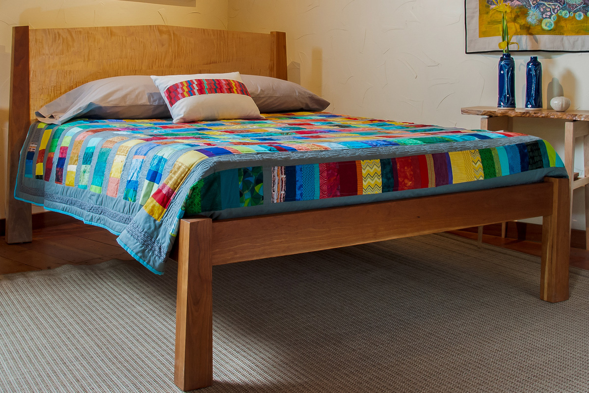 Cherry bed frame with quilted maple headboard panel.