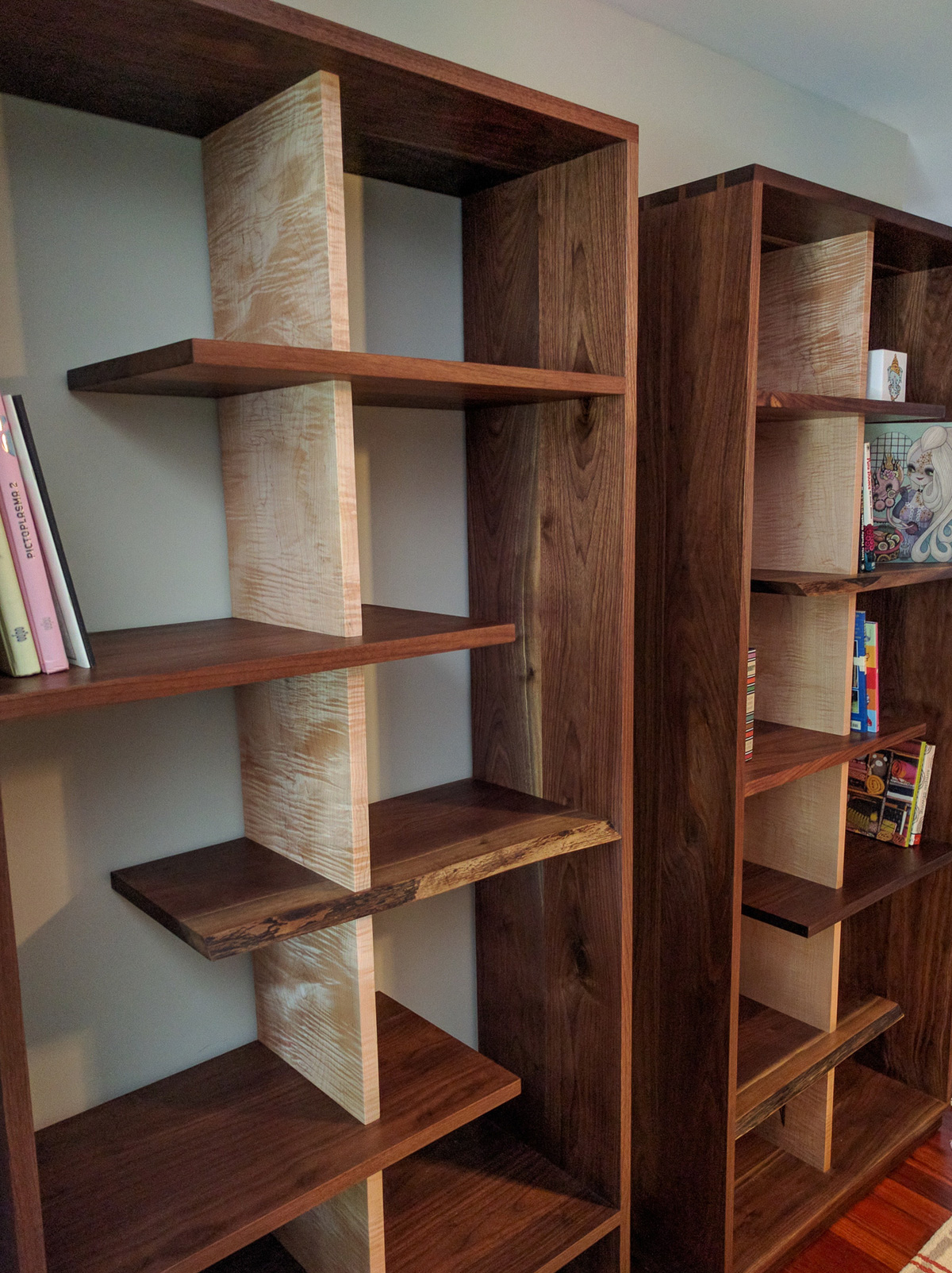 Dovetail walnut case with a live edge shelves incorporated and curly maple dividers.