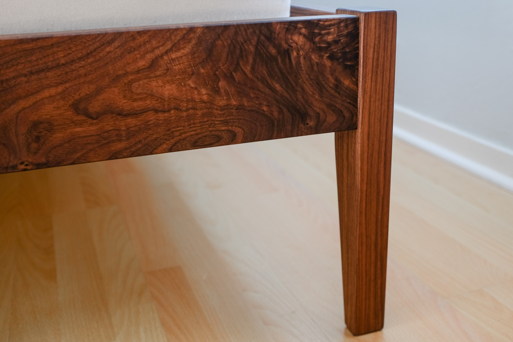 Detail of foot rail and foot post on walnut bed.
