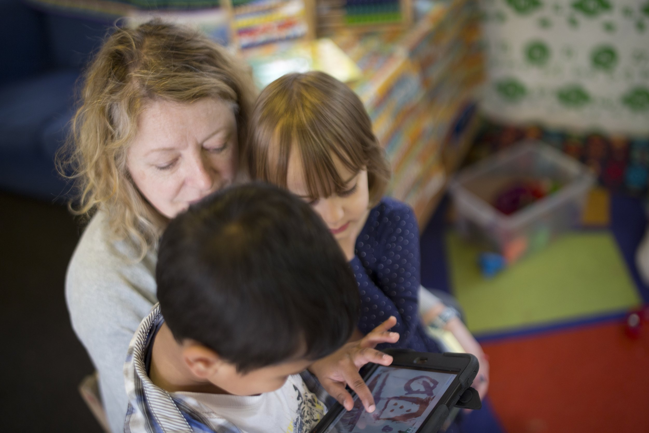 boy and girl with adult looking at ipad .jpg