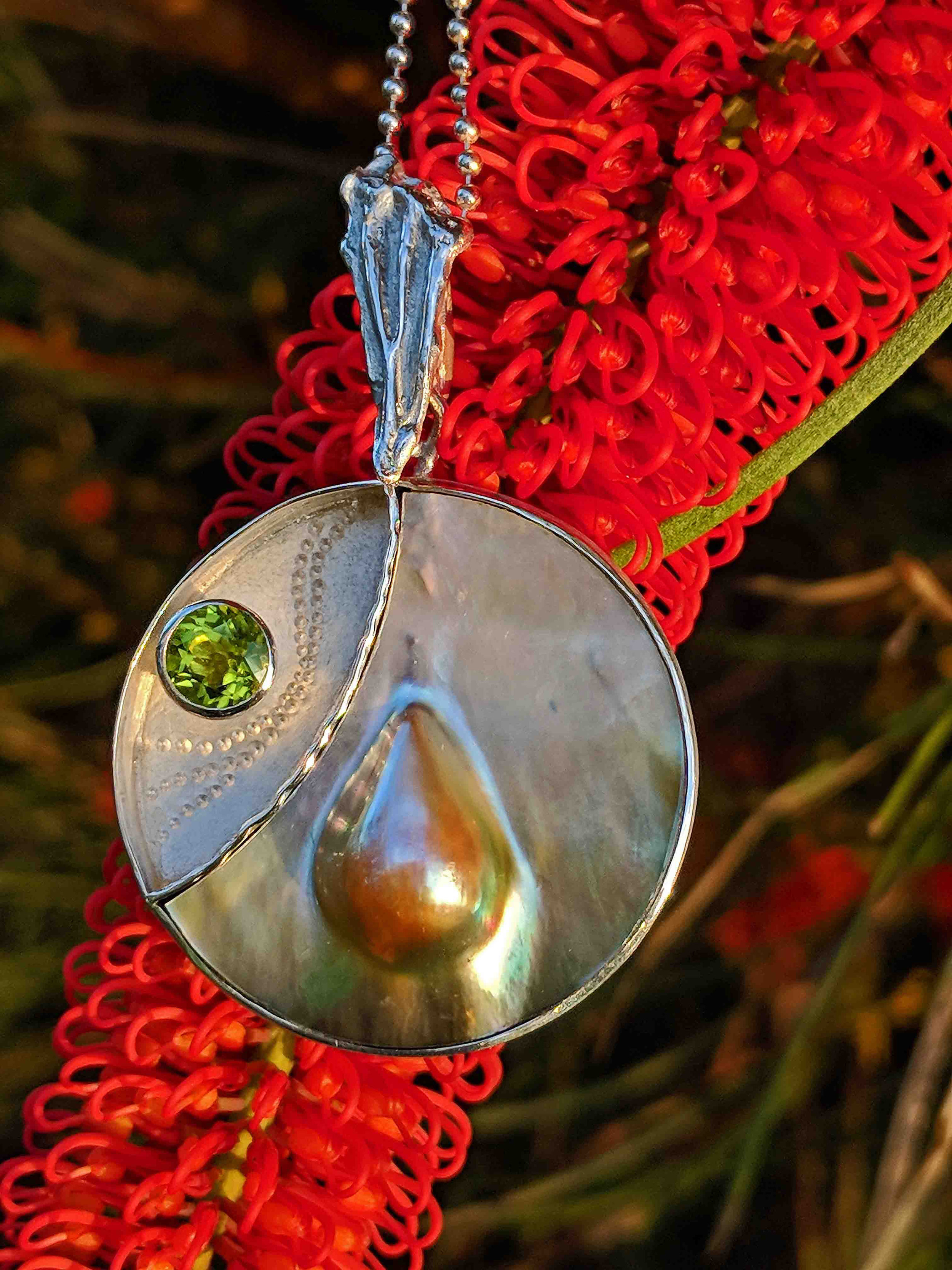 CAPE RANGE COLLECTION  Beautiful Peacock Abrolhos Mabe Pearl with Peridot and Signature Splice of Life Bail.  Inspired by the dawn walk over the dunes to the beach, marveling at the myriad of new tracks in the cool sand and watching as the sunrise brings colour to the world.