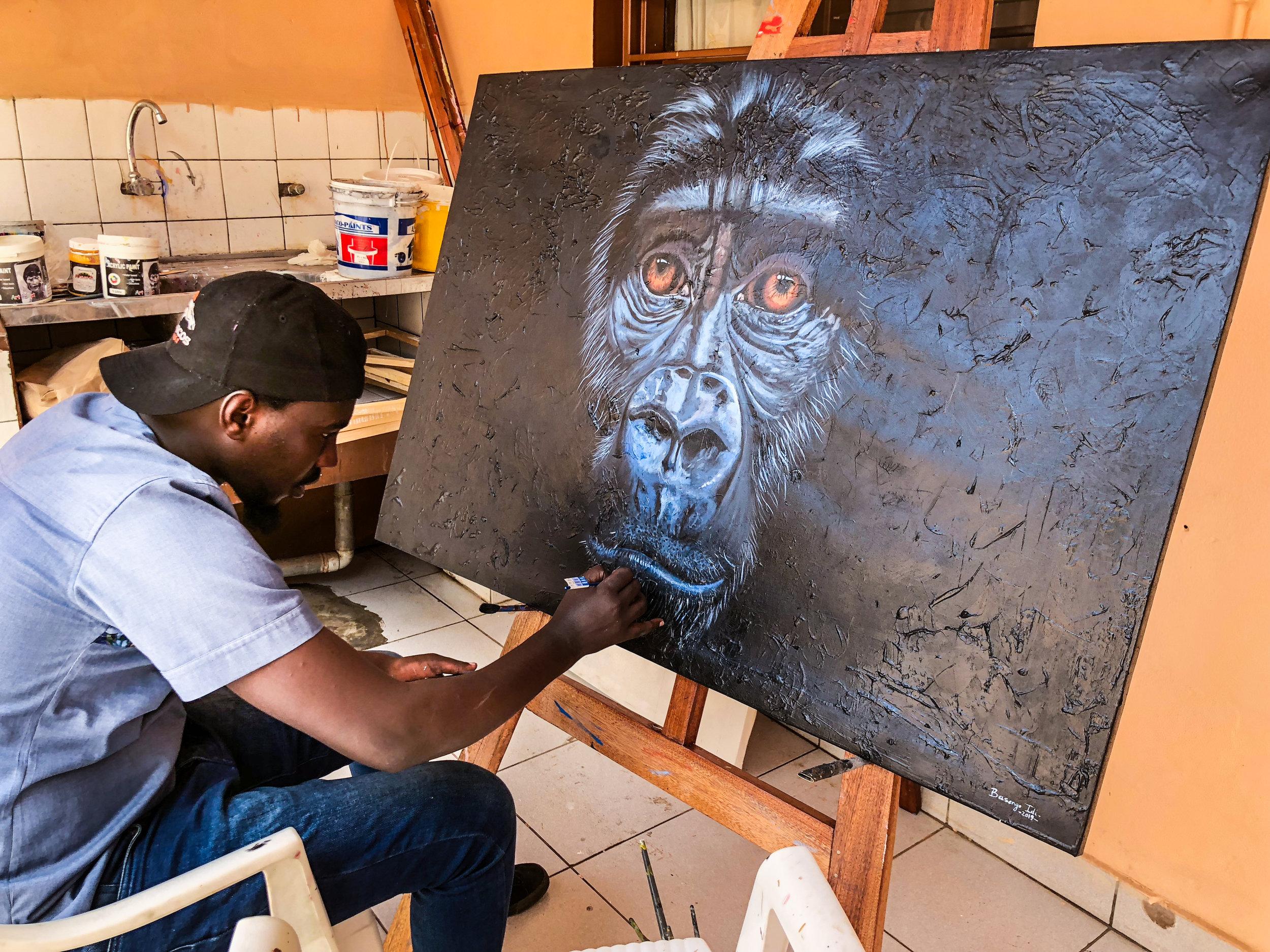 "Idi finishing up his acrylic piece titled ""Soul of Rwanda"""