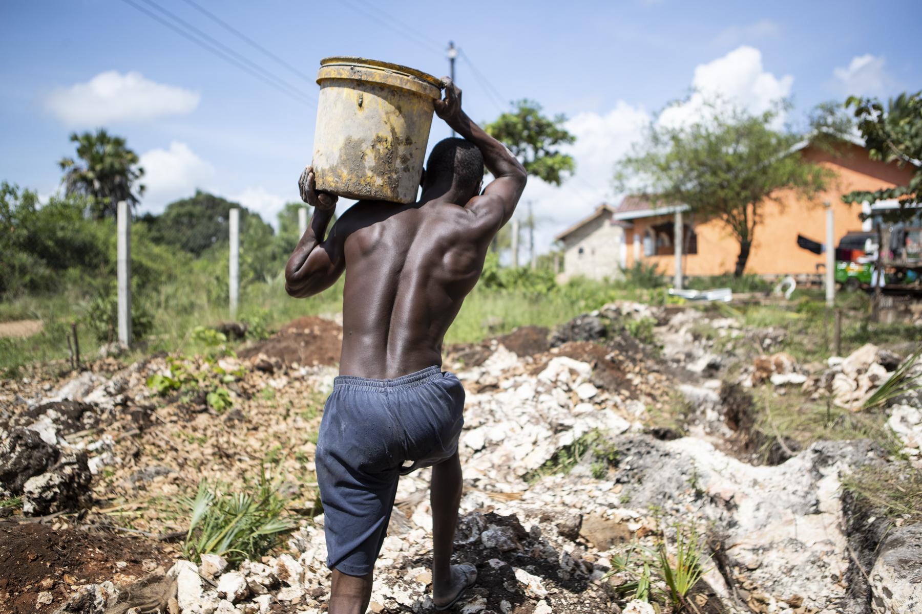 Die kräftigen Männer schleppen das Wasser für den Beton vom nahegelegenen Brunnen auf die Baustelle.