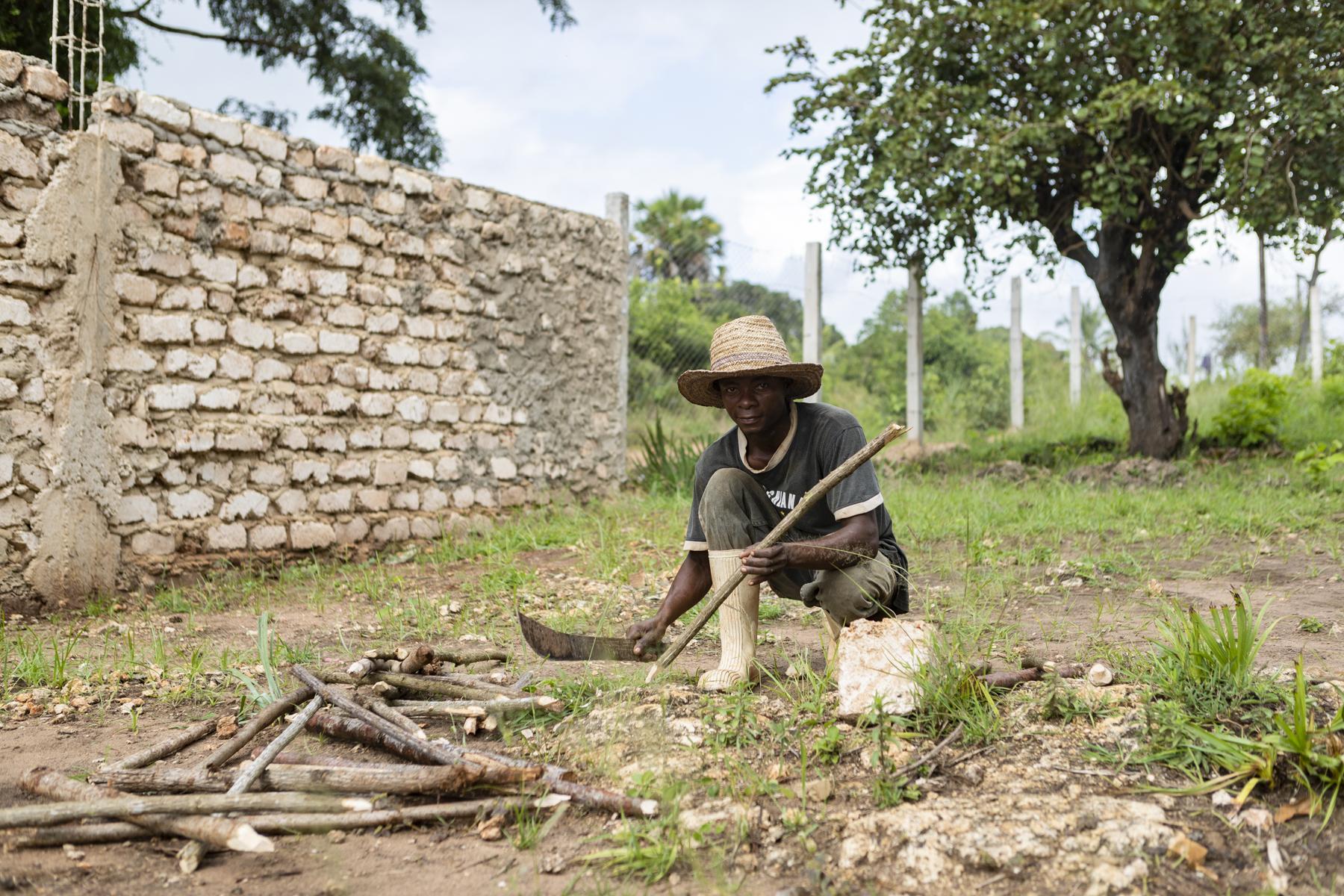 Ein Fundi spitzt die Pfähle für das Ausstecken des Baufeldes.