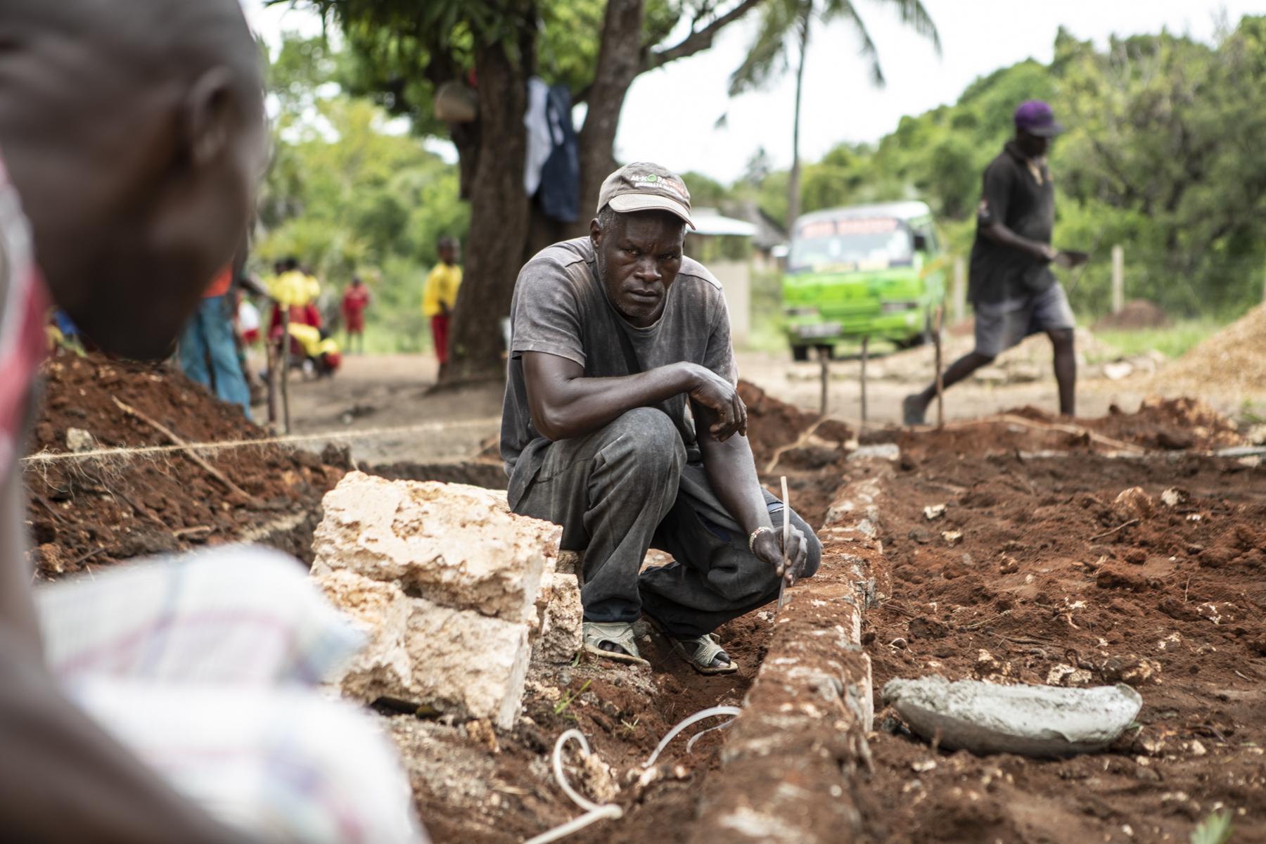 Um eine gerade Ebene zu erreichen greifen die Fundis zu den einfachsten physikalischen Mitteln: ein alter Wasserschlauch hilft dabei.
