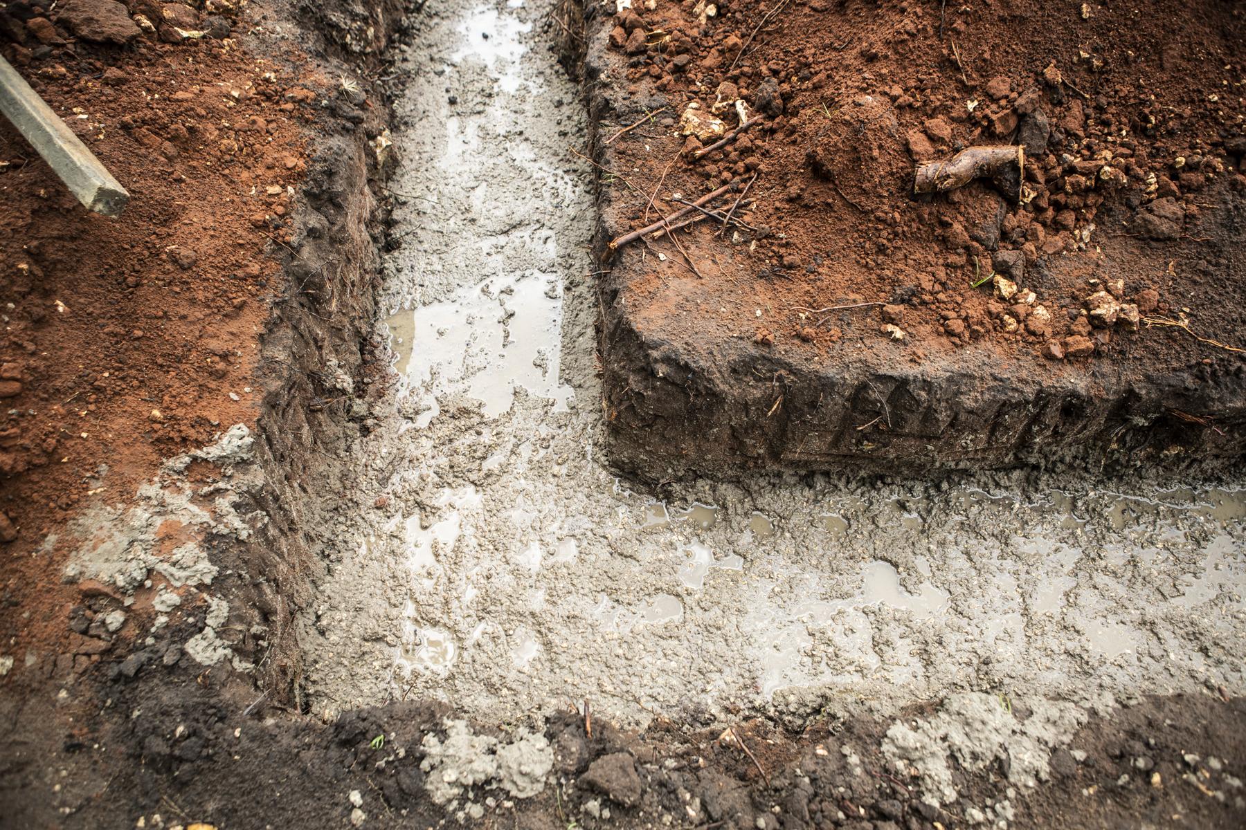 Das Fundament ist fertig gegossen. Starker Regen zwingt die Fundis zur Pause.