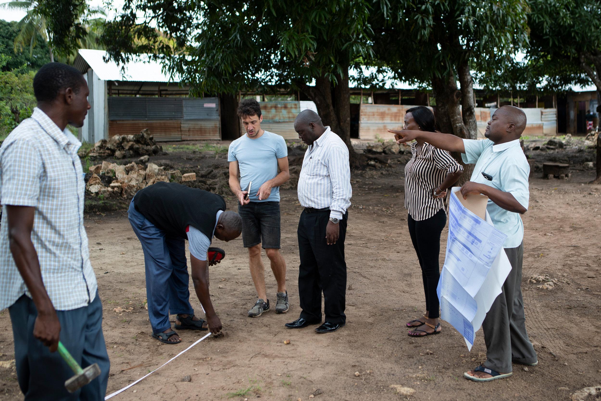 Milan Rohrer beim Vermessen des Geländes mit dem Bauherrn, Bauunternehmer und Architekten. Foto: Karen Yee