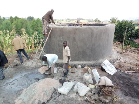 A community rain water harvesting water tank under construction in Nzogera village