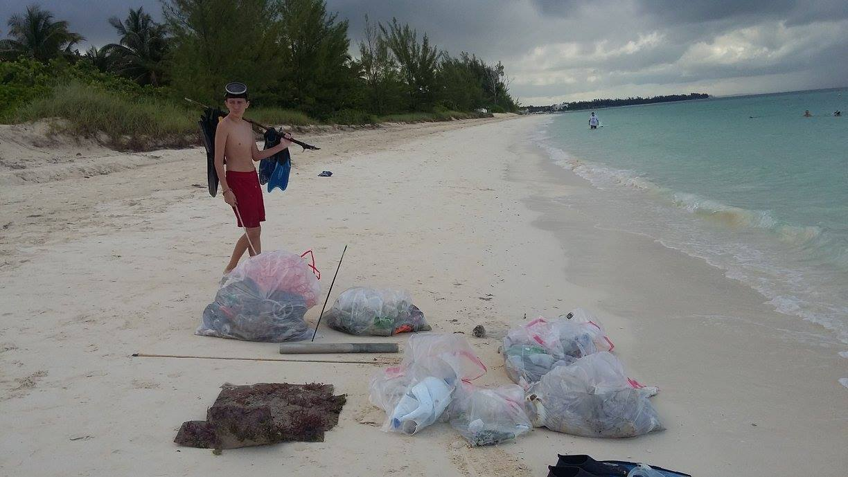 Justin Snisky II surveys the marine  debris collected by the EARTHCARE volunteers.jpg