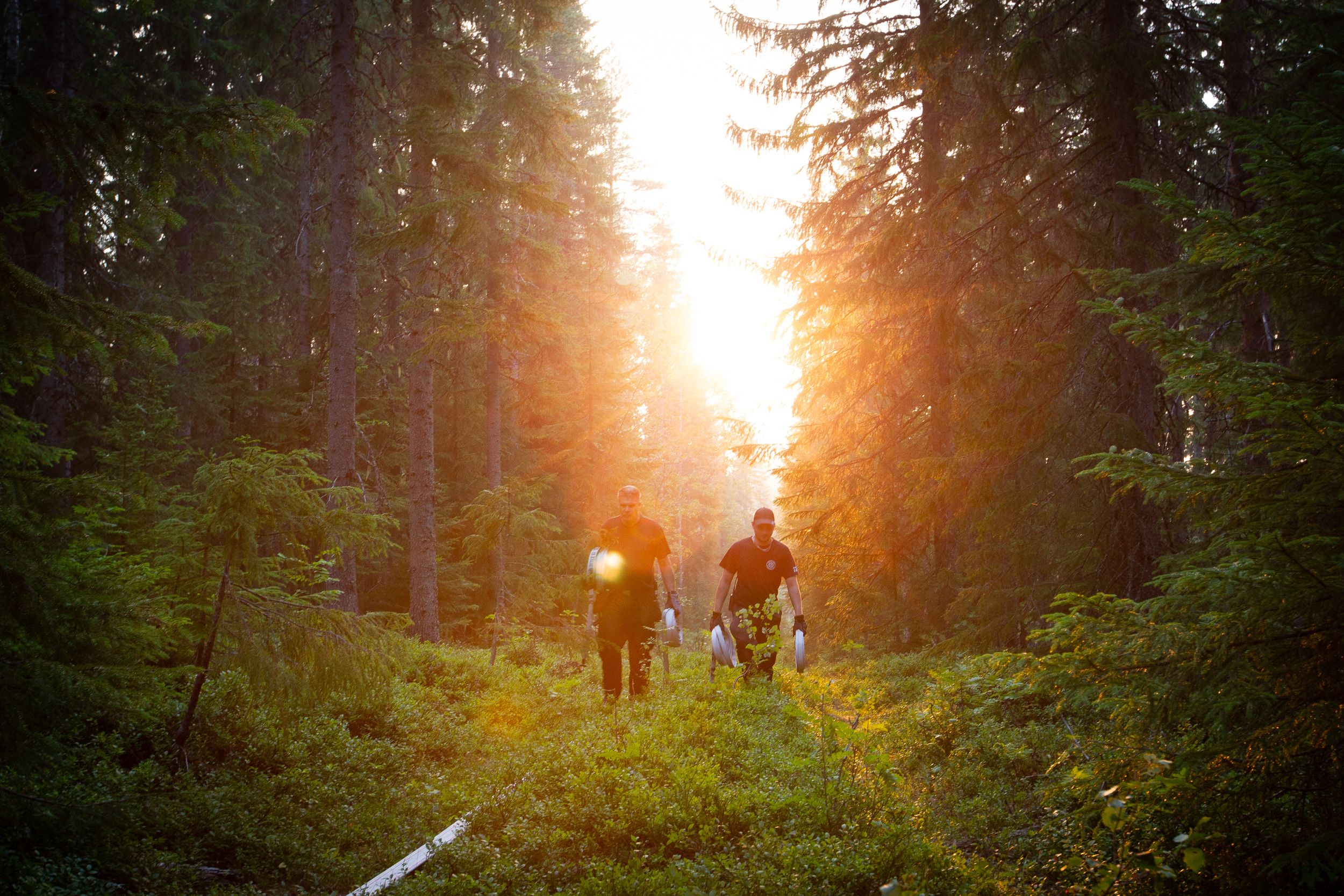 Two firefighters carrying extra fire hoses in the evening sun to combat a forest fire in Hälsingland, Sweden.