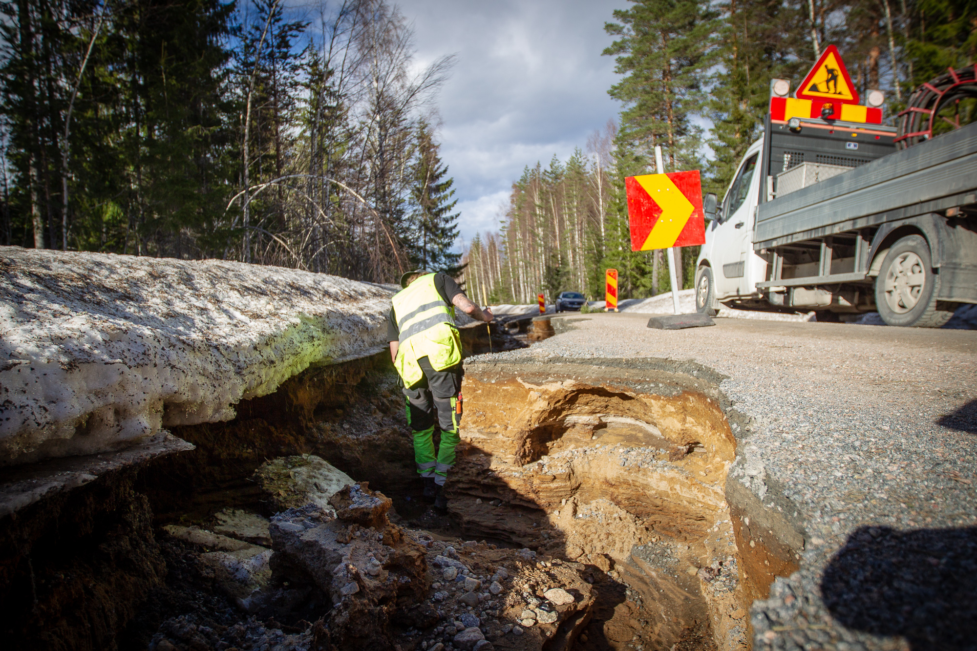 A municipal department of transportation worker inspects the damage to a regional road west of Hudiksvall where half the road had washed away.