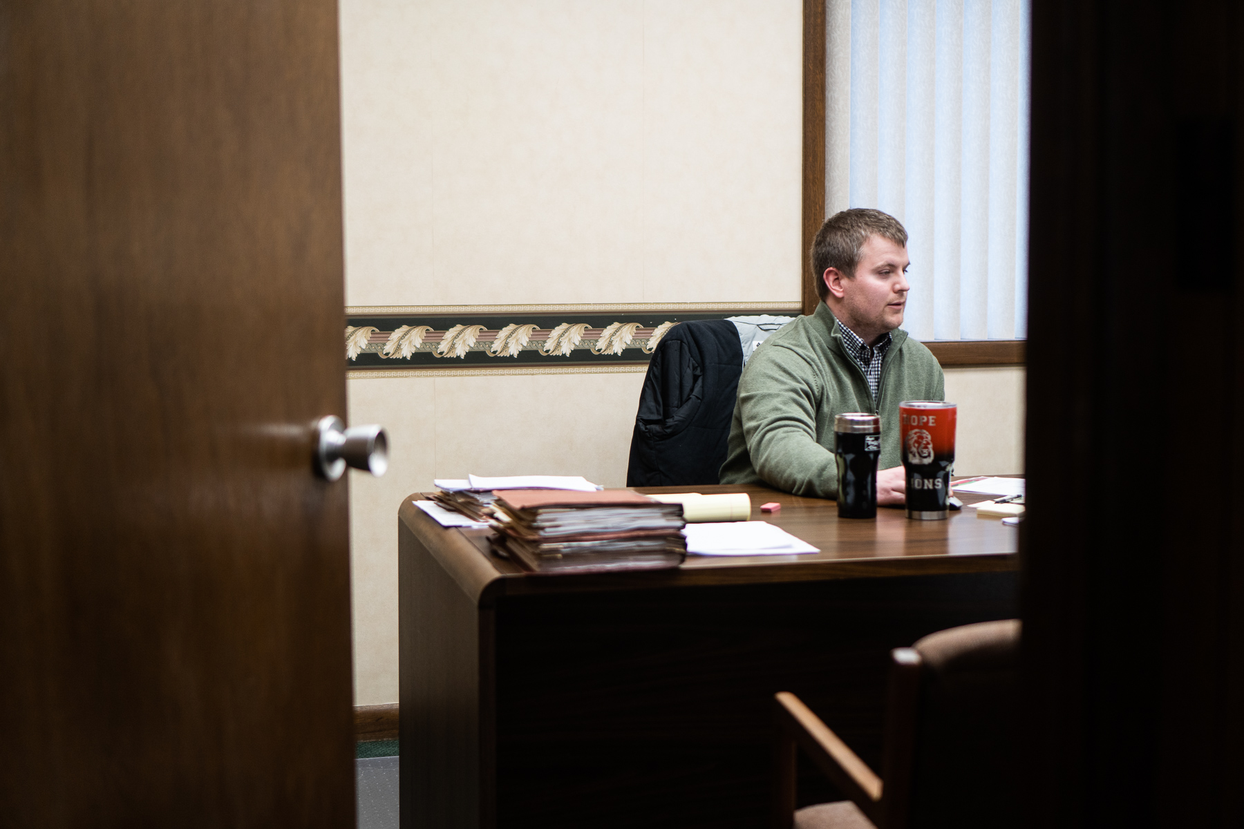 Dillon Cook, one of Lucas Hicks' friends and pallbearer at the funeral, sits in his office at the First National Bank of Hope, Kansas.