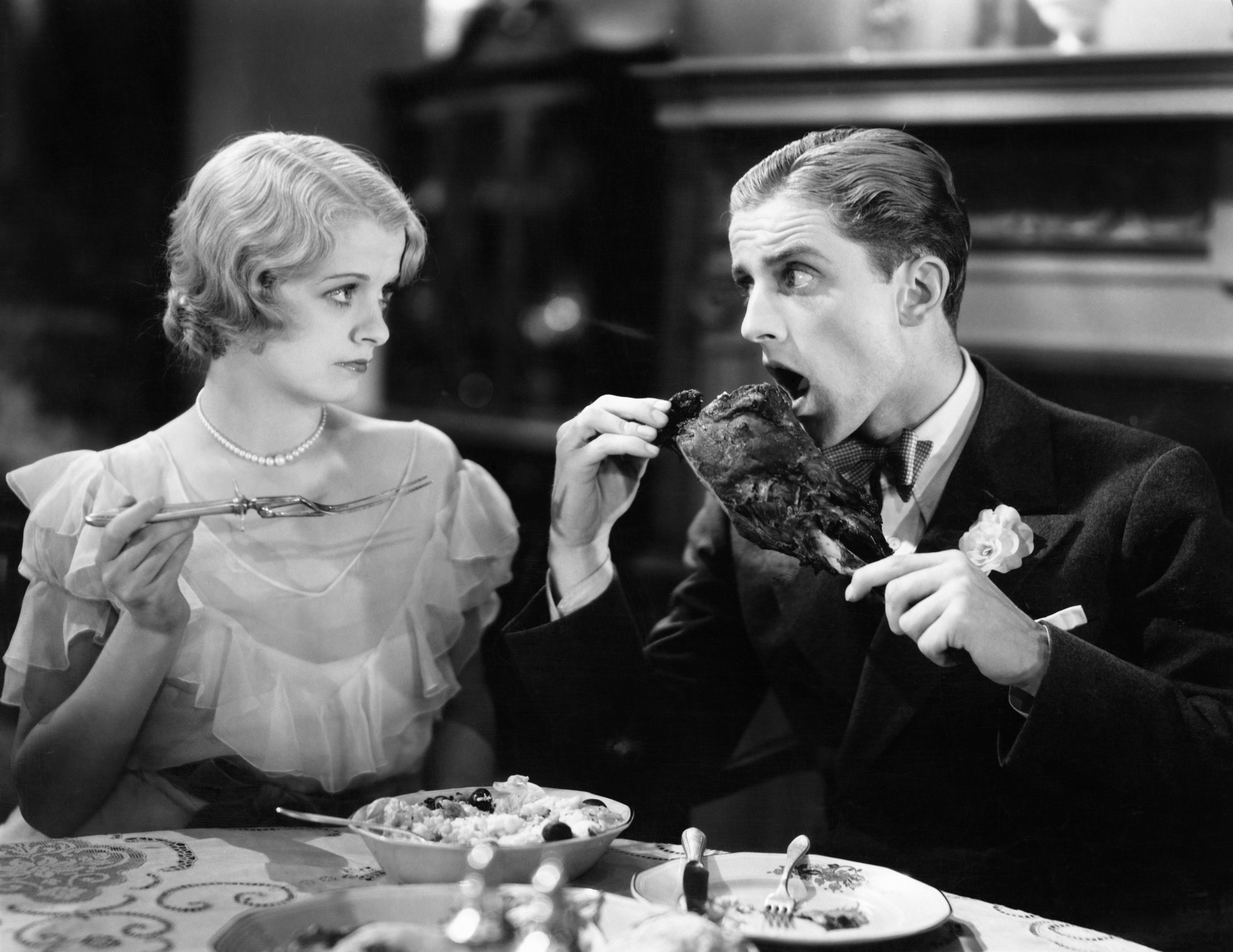 man eating with hands in front of woman