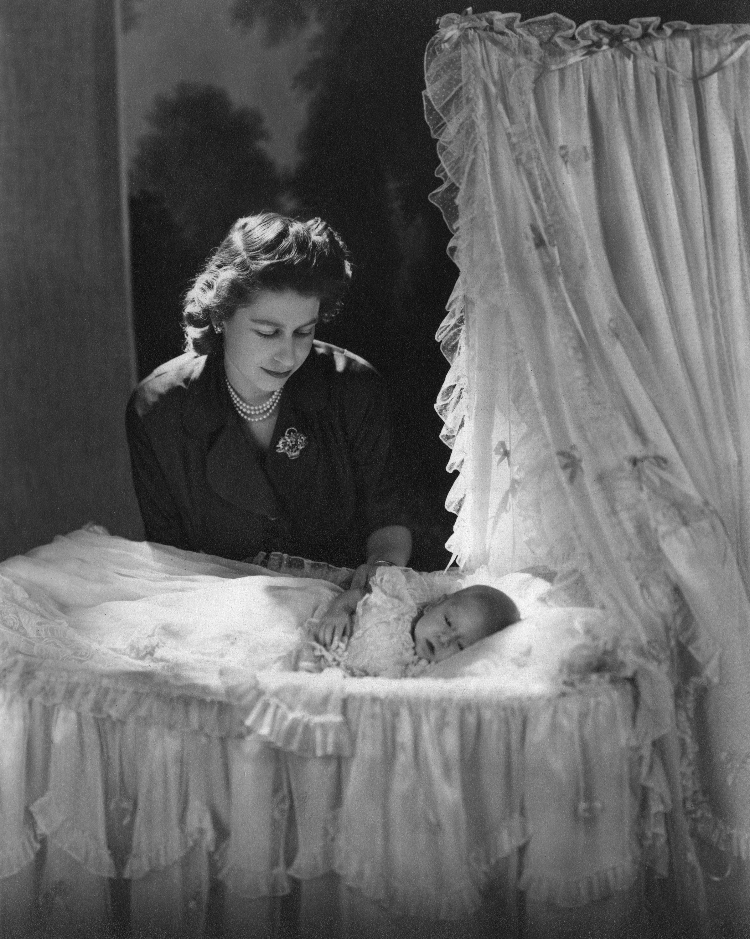 Queen E_HTRA596_VV074_H.JPGPrincess Elizabeth (Queen Elizabeth II) gazes down at her firstborn child, Prince Charles (Prince of Wales) lying in his cradle.