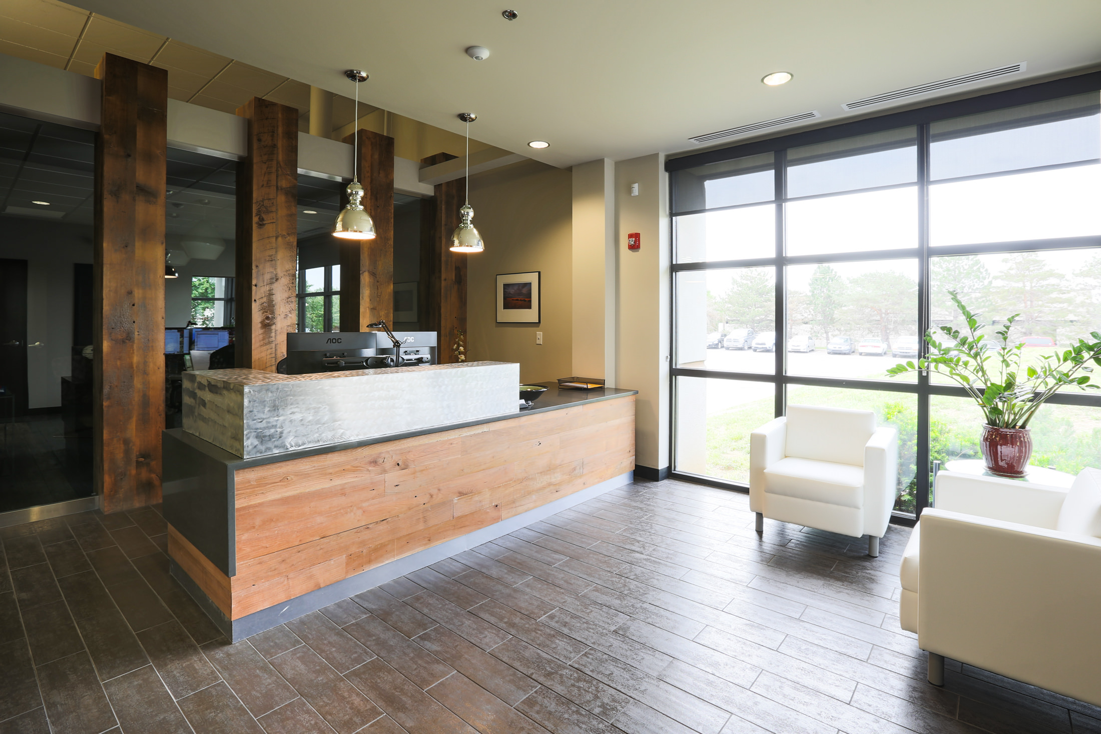 Brushed metal and reclaimed wood make a bold statement in the lobby of Power Source's newly-remodeled office and warehouse space in Lenexa, KS