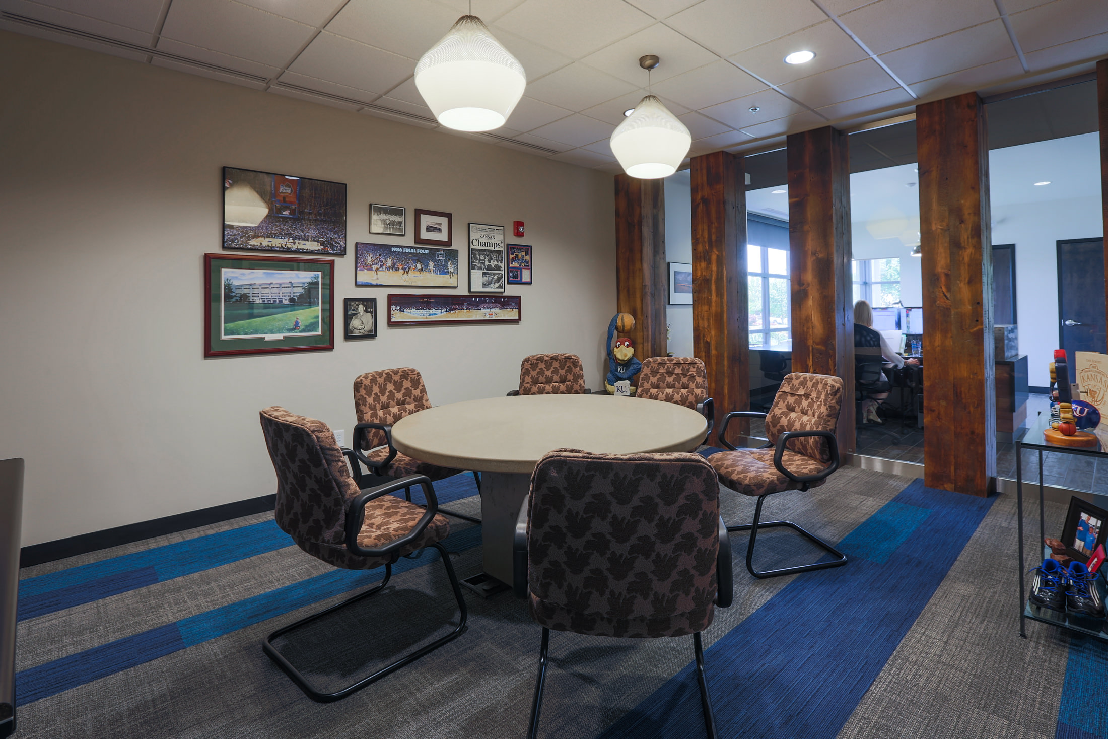 A conference room features KU memorabilia and reclaimed wood columns
