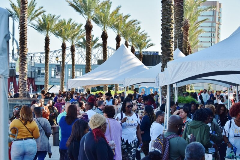 Crowd on plaza with palm tree stretch of tent.jpg