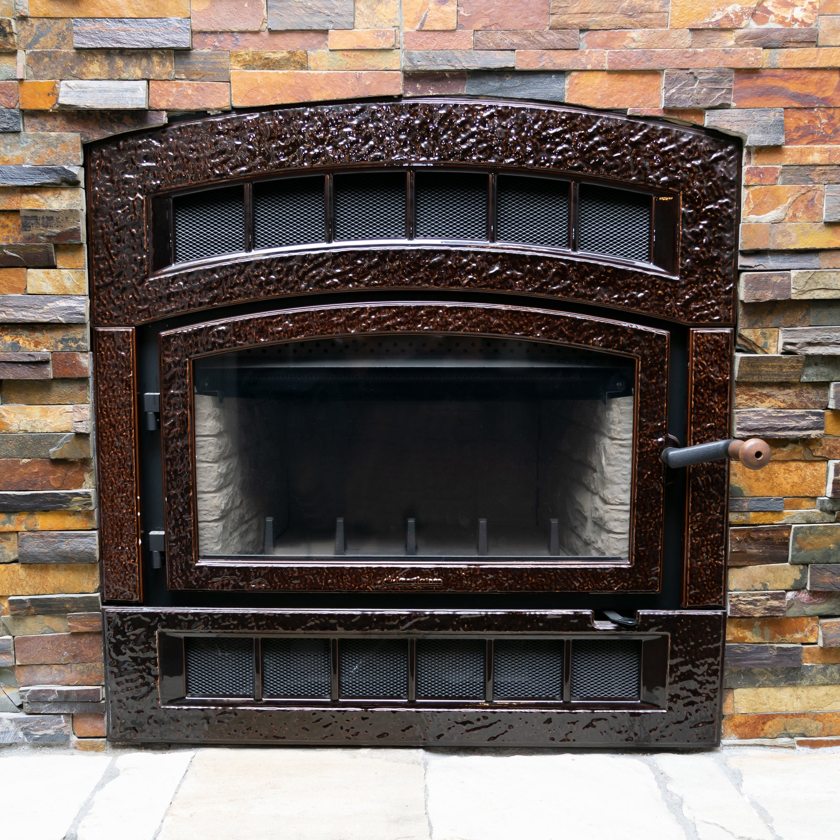 "Hearthstone Montgomery 75 - ‧ Wood Fireplace - 75,000 BTU‧ Brown Majolica Enamel‧ 2.5 cu ft Firebox‧ 20"" Logs‧ Optional heat-circulating blower‧ Cast Iron Faceplate‧ Single-door design‧ Ledgestone interior panel‧ Choice of Black or Brown Enamel"