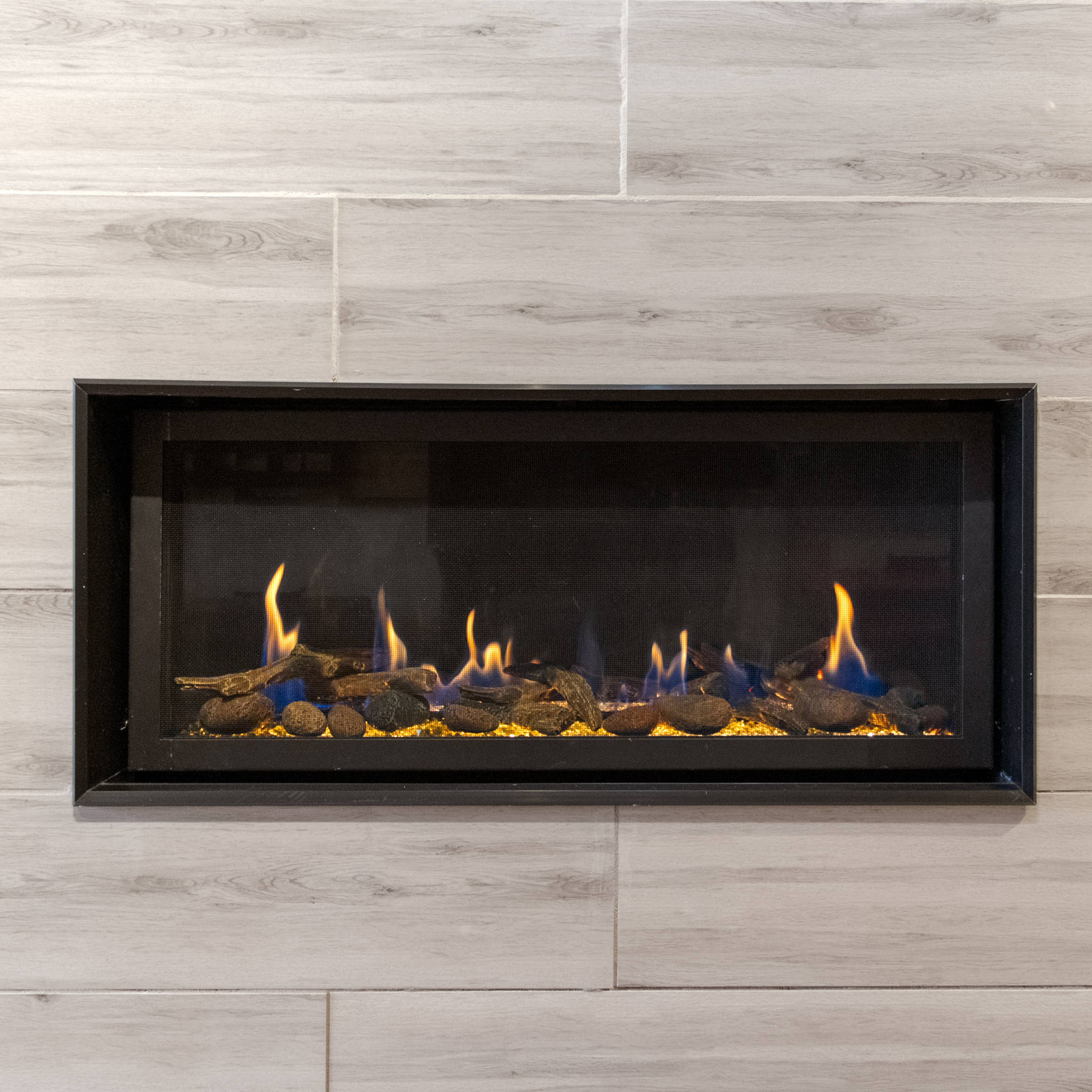 FireplaceX 3615 - ‧ Direct Vent Gas Fireplace - 33,000 BTU‧ Black Porcelain Enamel Fireback‧ Tile Trim Kit‧ Driftwood Twigs and Stones Fyre-Art‧ Black Glass Burner Media‧ Proflame2 Full Function Remote Control‧ Fan‧ Choice of glass – driftwood – logs‧ Perfect for large bedrooms – family rooms – office‧ Most Popular Linear Fireplace