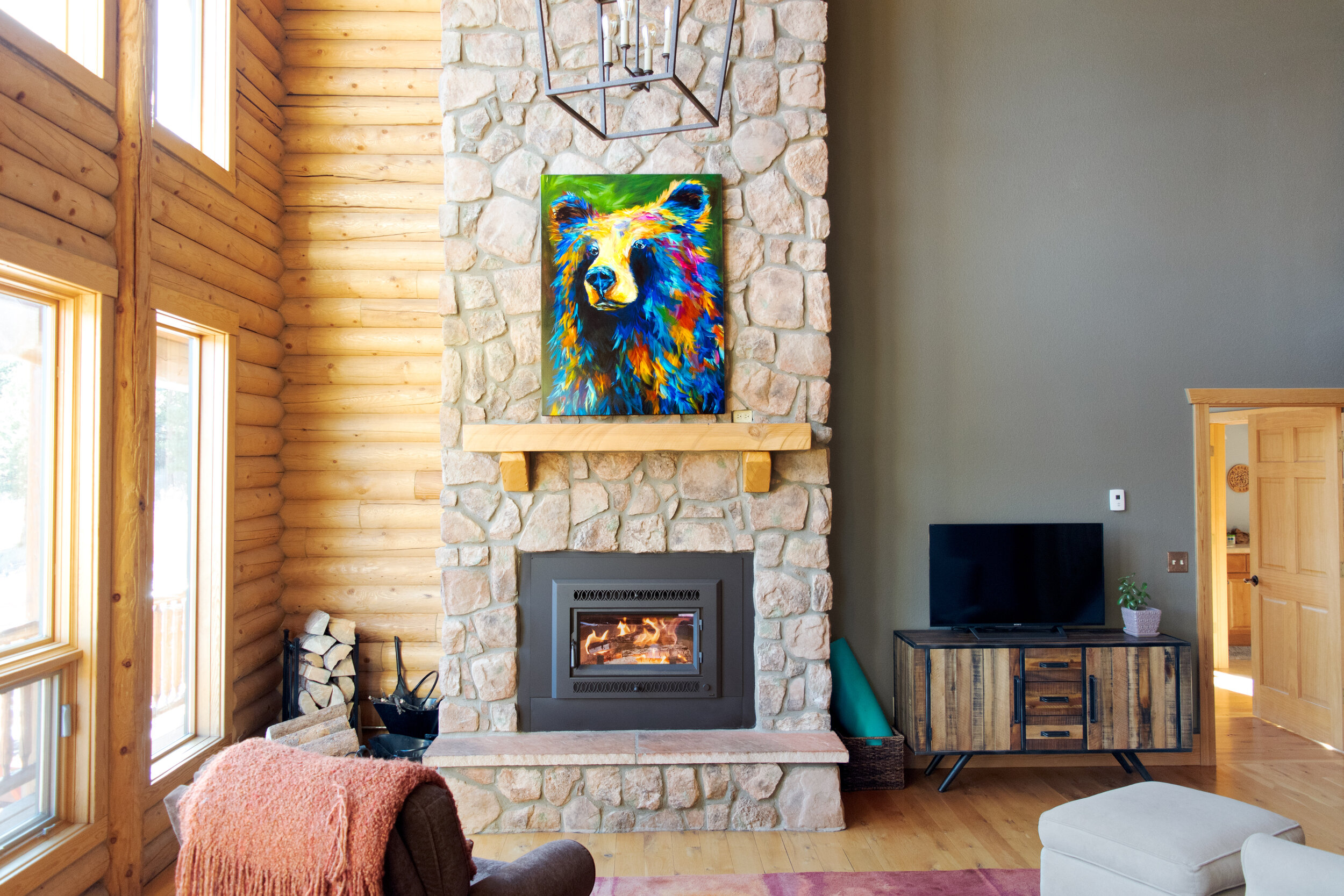 A FireplaceX Medium Flush Wood Insert in a mountain home with a painting of a bear above the mantel.