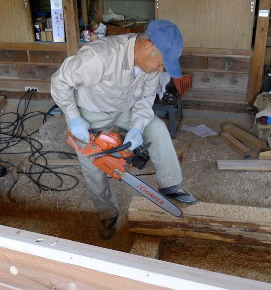 Murakami using a chainsaw to rough out the stem. Note the footwear.