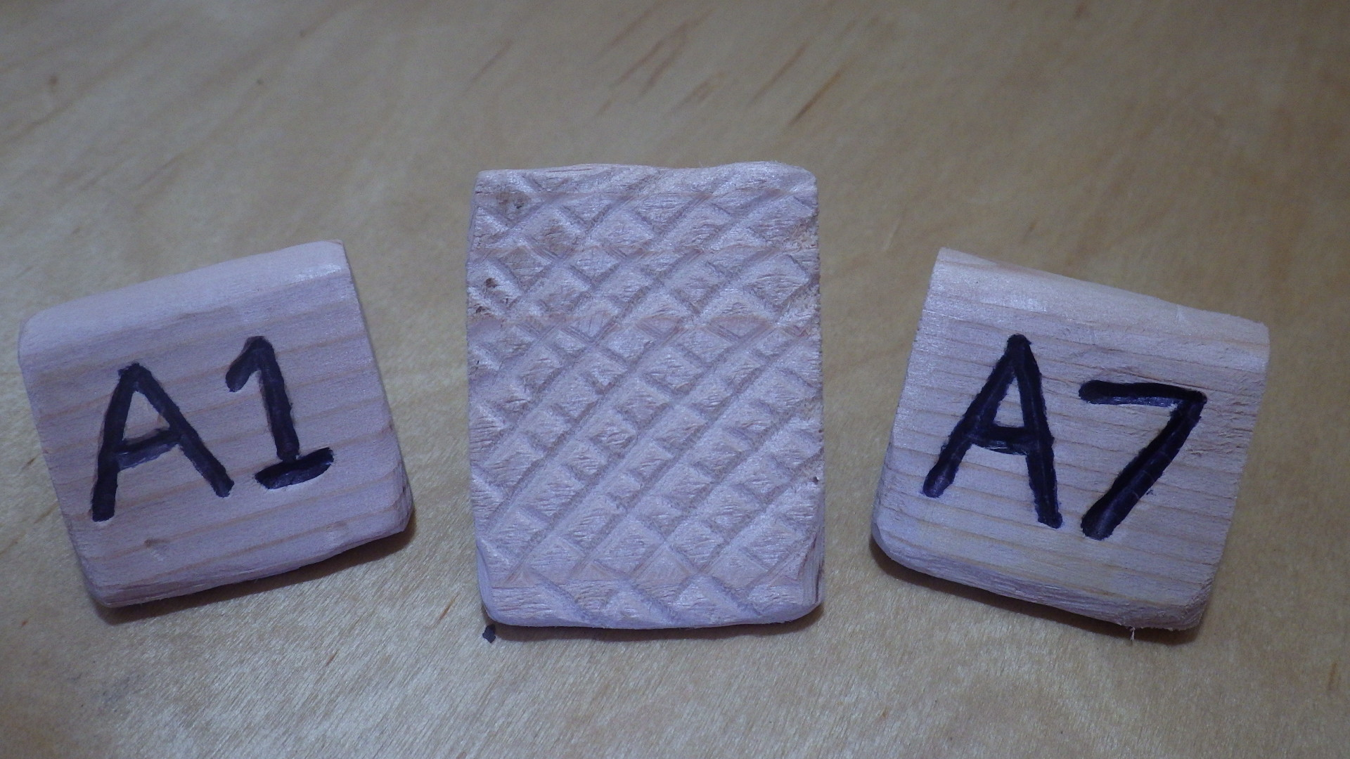 Cedar hat tags showing inset lettering and scoring pattern on bottom