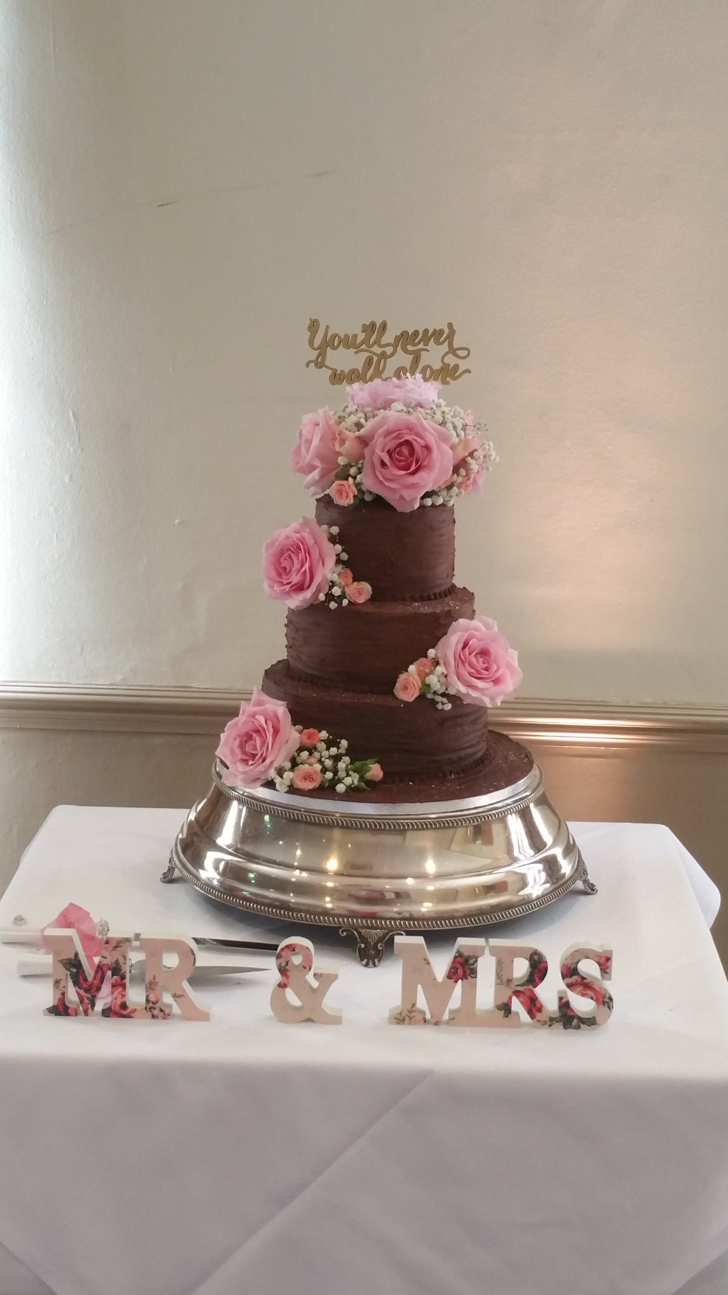 Indulgent chocolate - 3 tiers of delicious chocolate ganache wedding cake.  Finished with a rustic look and arrangements of pretty fresh flowers.