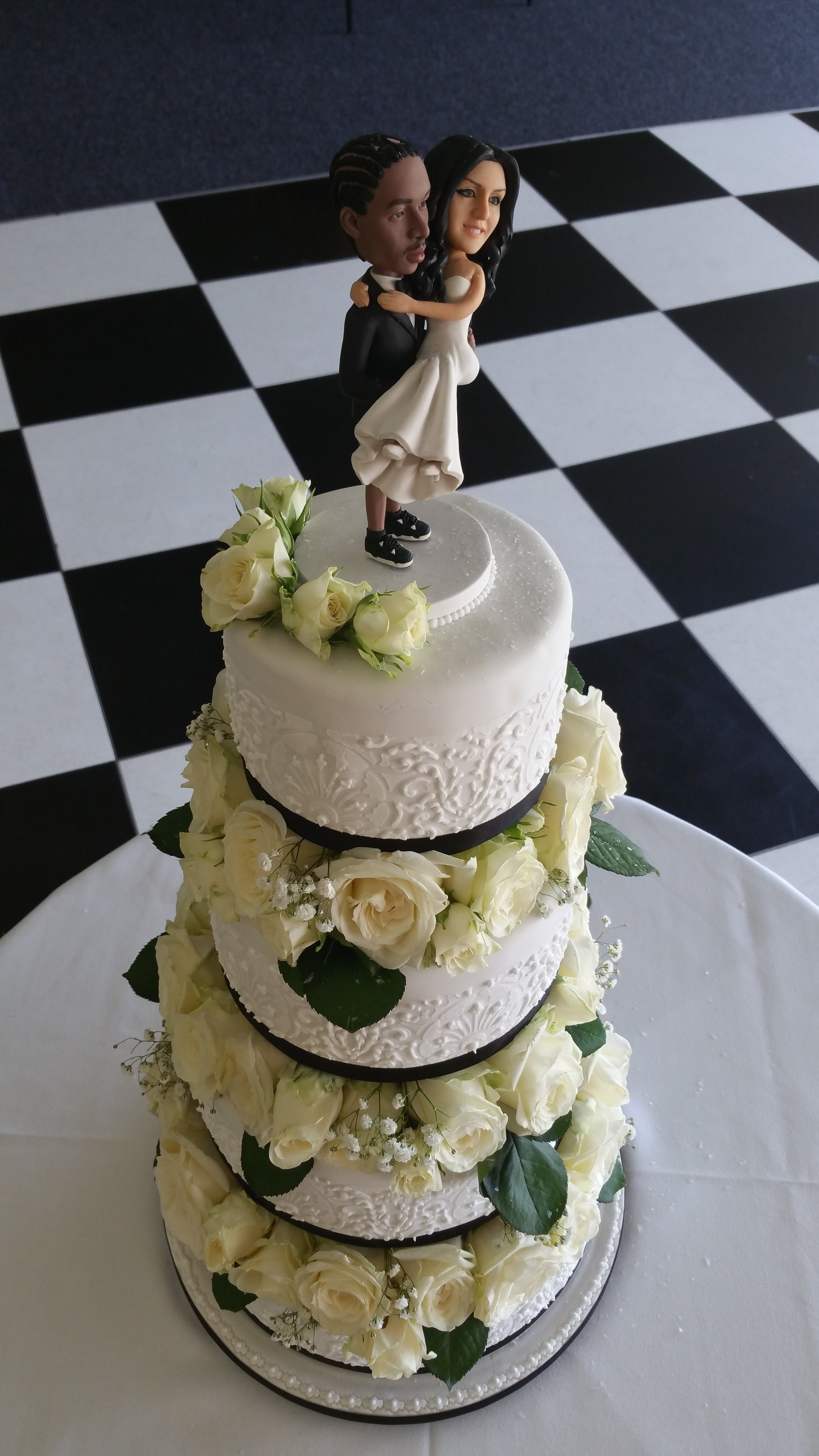 Fun and stylish - Stunning 4 tier cake with overpiped stencils, decorated with fresh flowers and bride's own cake topper.