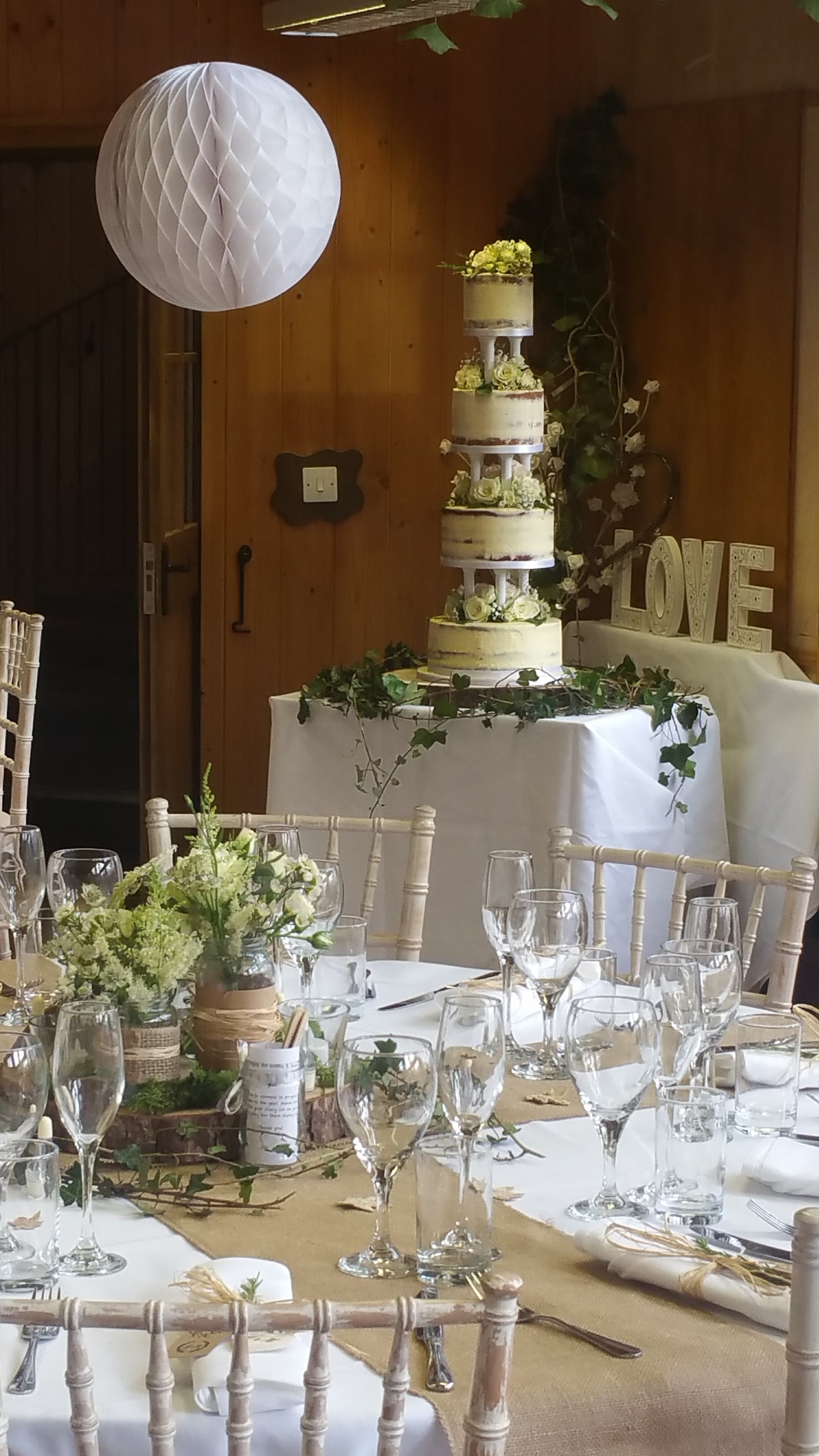 4 tier semi naked wedding cake - A wonderful take on a traditional yet modern cake. Pillars and a semi naked cake in 4 different flavours matched the theme so well.
