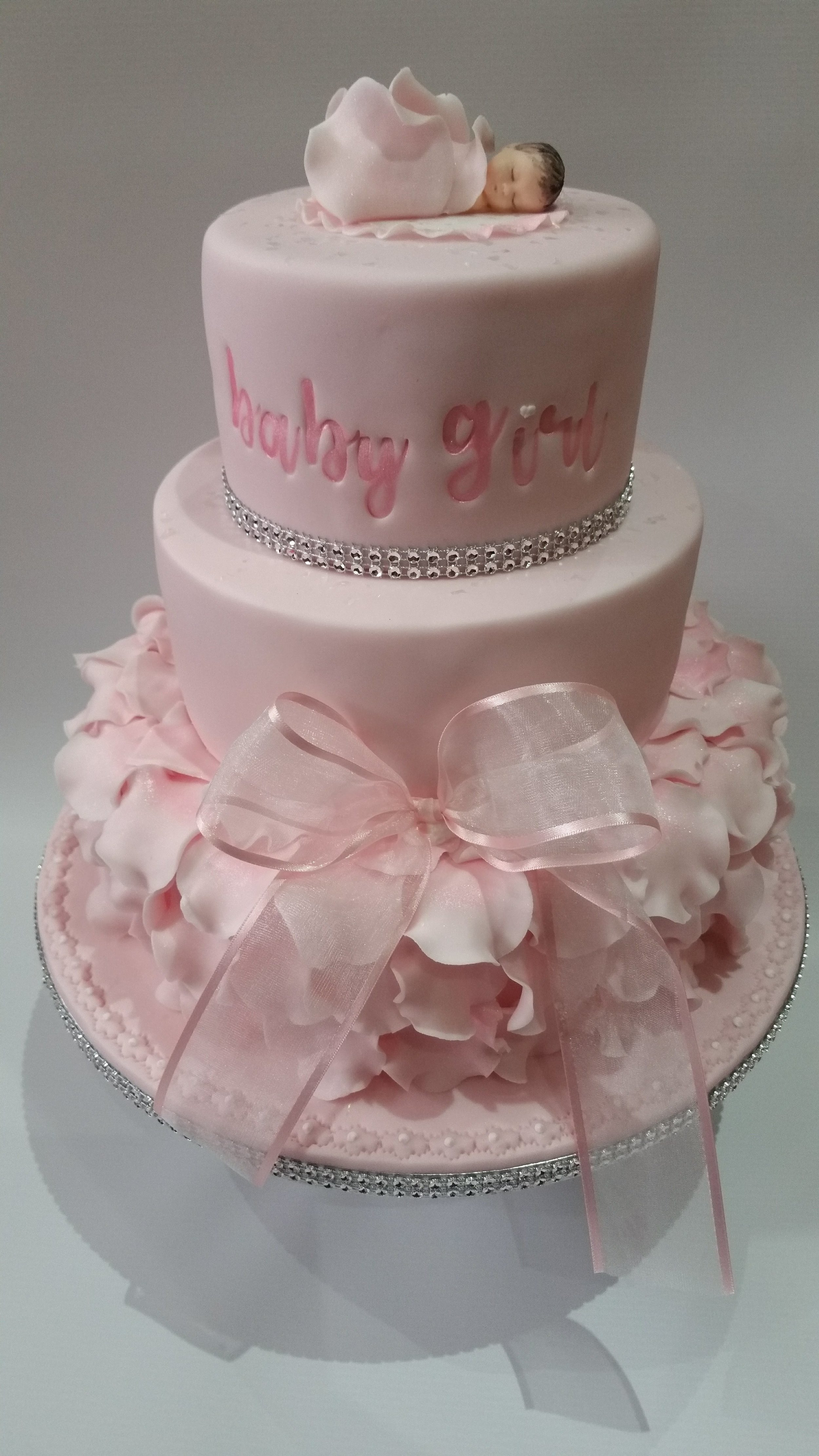 Baby shower - A really pretty cake with hand made rose petals, bow and baby girl model, with trendy hand painted writing and diamante bands.