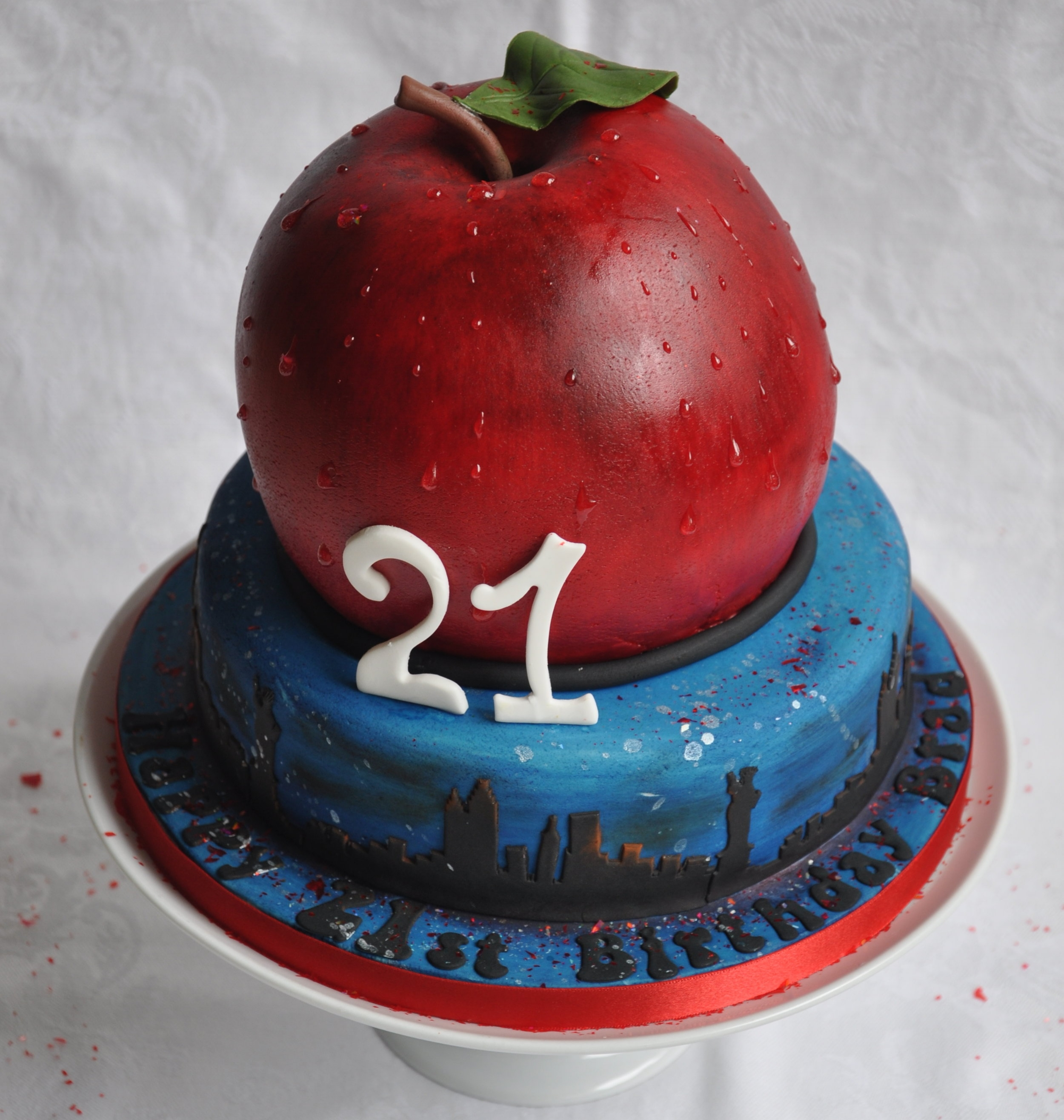 Big Apple - A cake made for a milestone birthday, Brad's parents gave him this cake as a clue to where he was going for a wonderful holiday to celebrate his birthday – any idea?A two tier cake, the apple was covered and painted to look realistic with drips of dew and a lifelike leaf. Placed over a New York night sky, with silhouettes of the Statue of Liberty and Empire State Building this cake is sure to be a big hit.