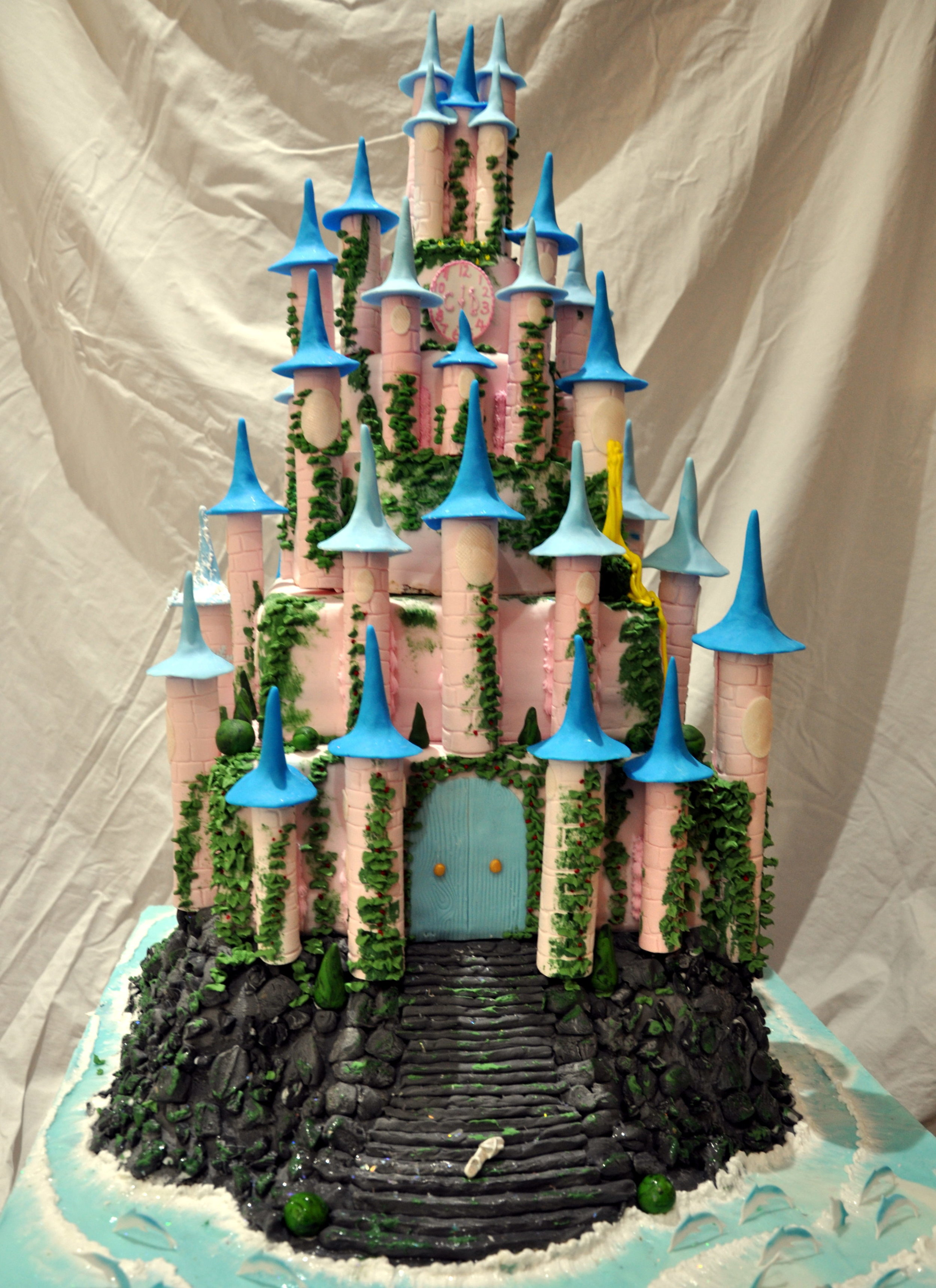 Fairy tale castle - An amazing five tier wedding cake for a couple with a fun outlook on life.  The fairy tale castle has a clock striking at the time of the ceremony, a glass slipper discarded on the steps and dolphins playing in the sea in tribute to the event.For an extra surprise, each tier is a different flavour.