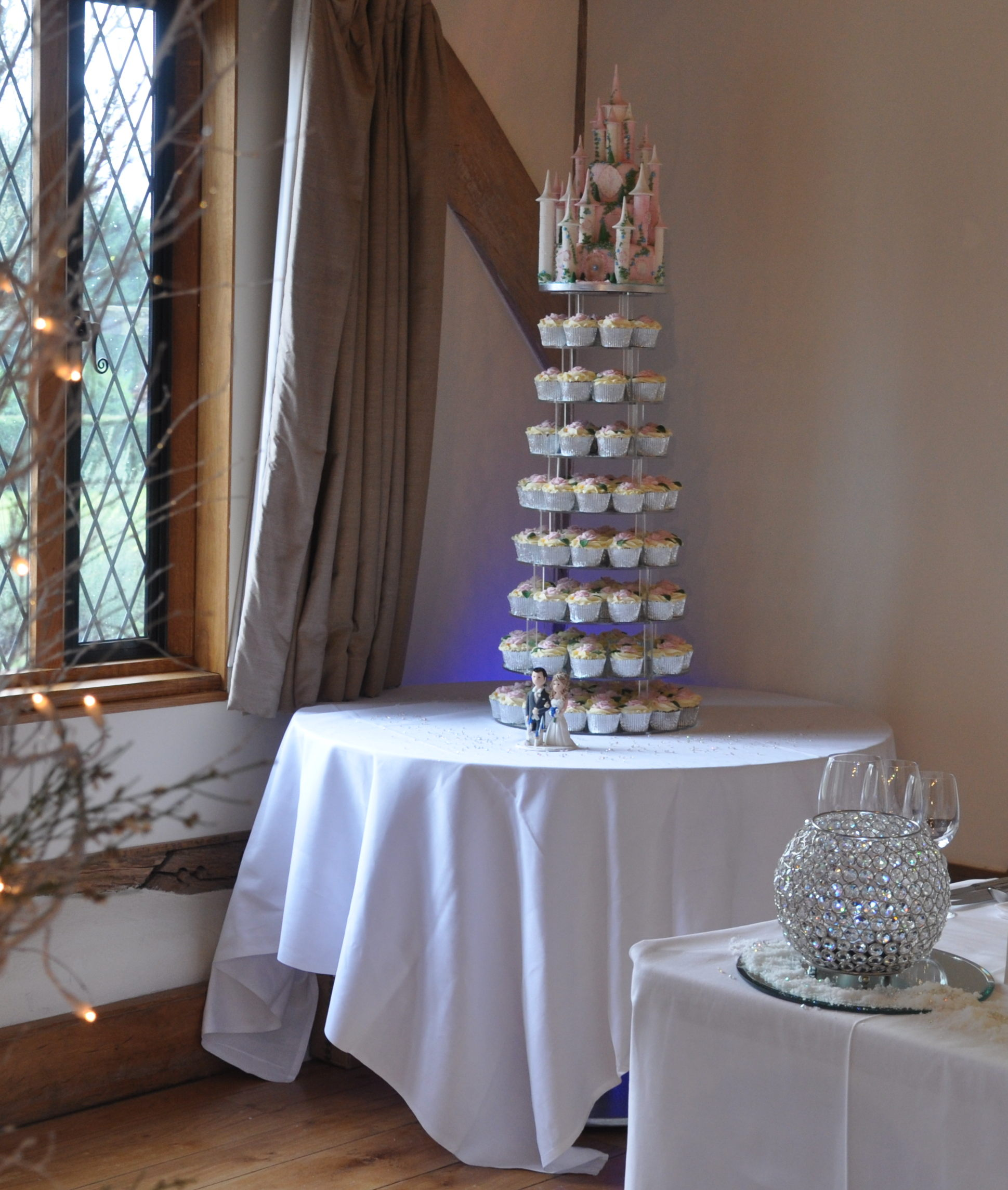 A fairy tale - A wonderful wedding cake cupcake tower, topped with an intricate fairy tale castle cake topper, complimenting Emma's colours. Each of the 126 cupcakes is individually made and decorated with ivory rose swirls and finished with a hand made rose and leaf. Shown on our mirror stand, this cake is truly stunning and so pretty.