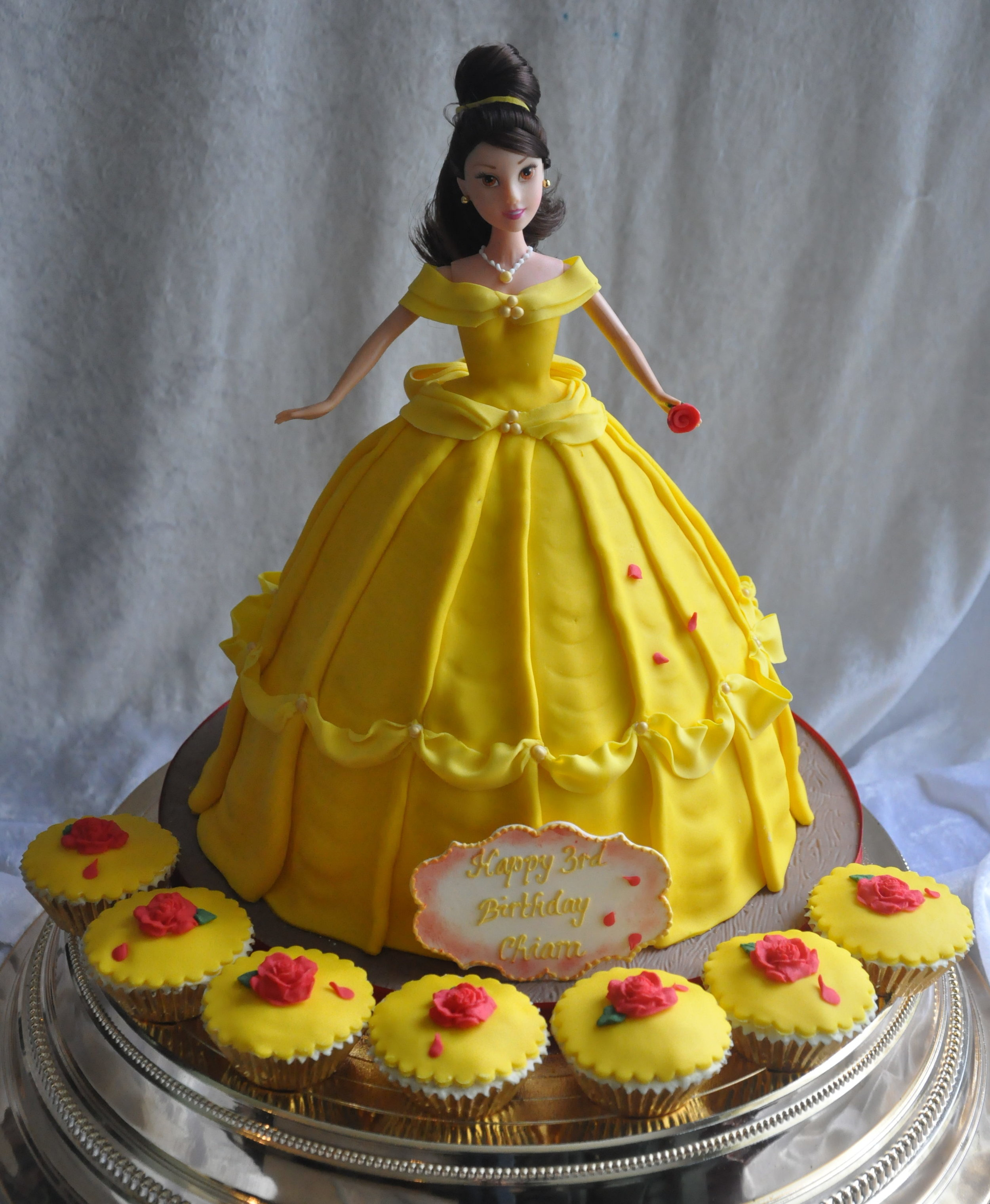 Beauty Belle - Our beautiful Belle cake. Hand made in delicious vanilla sponge, butter cream and jam, finished with sugar icing. Every detail is perfect, the swish of her gown, the swag details on the dress and complete with a sugar rose and its falling petals, A memorable cake with matching cupcakes. A wonderful centrepiece for your Princess Party.