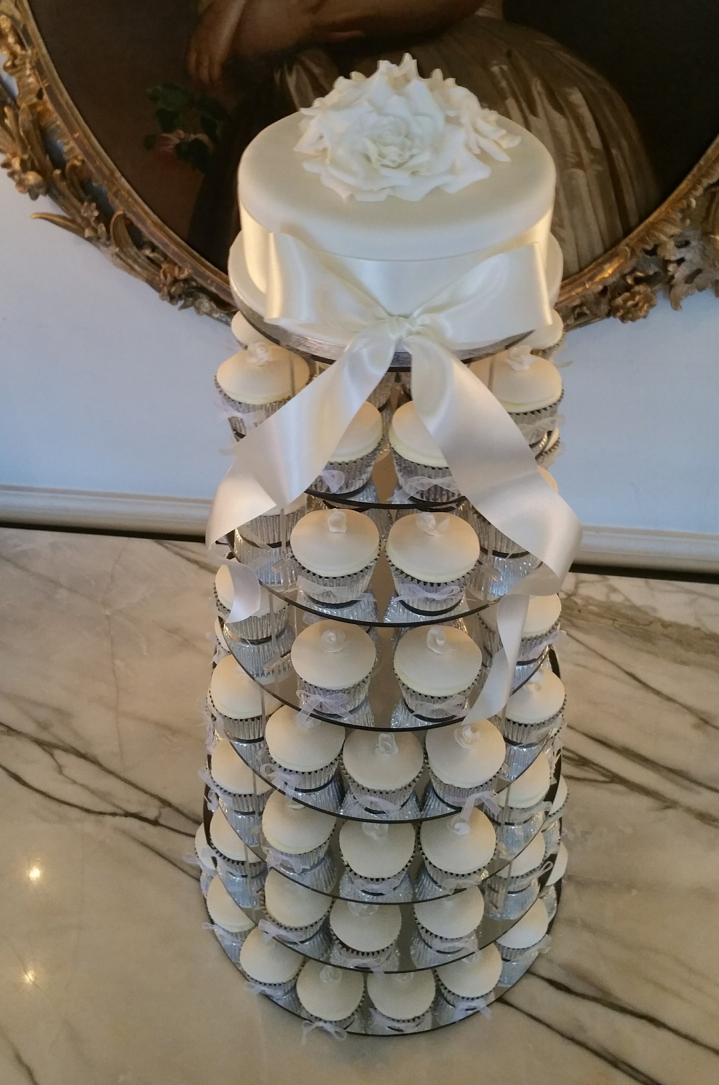 Elegant cupcake tower - So pretty, this elegant tower of hand made cupcakes and top cake was displayed at Cliveden.  Each cake featured a hand made rose and bow.  The top cake had a gorgeous arrangement of white sugar roses.