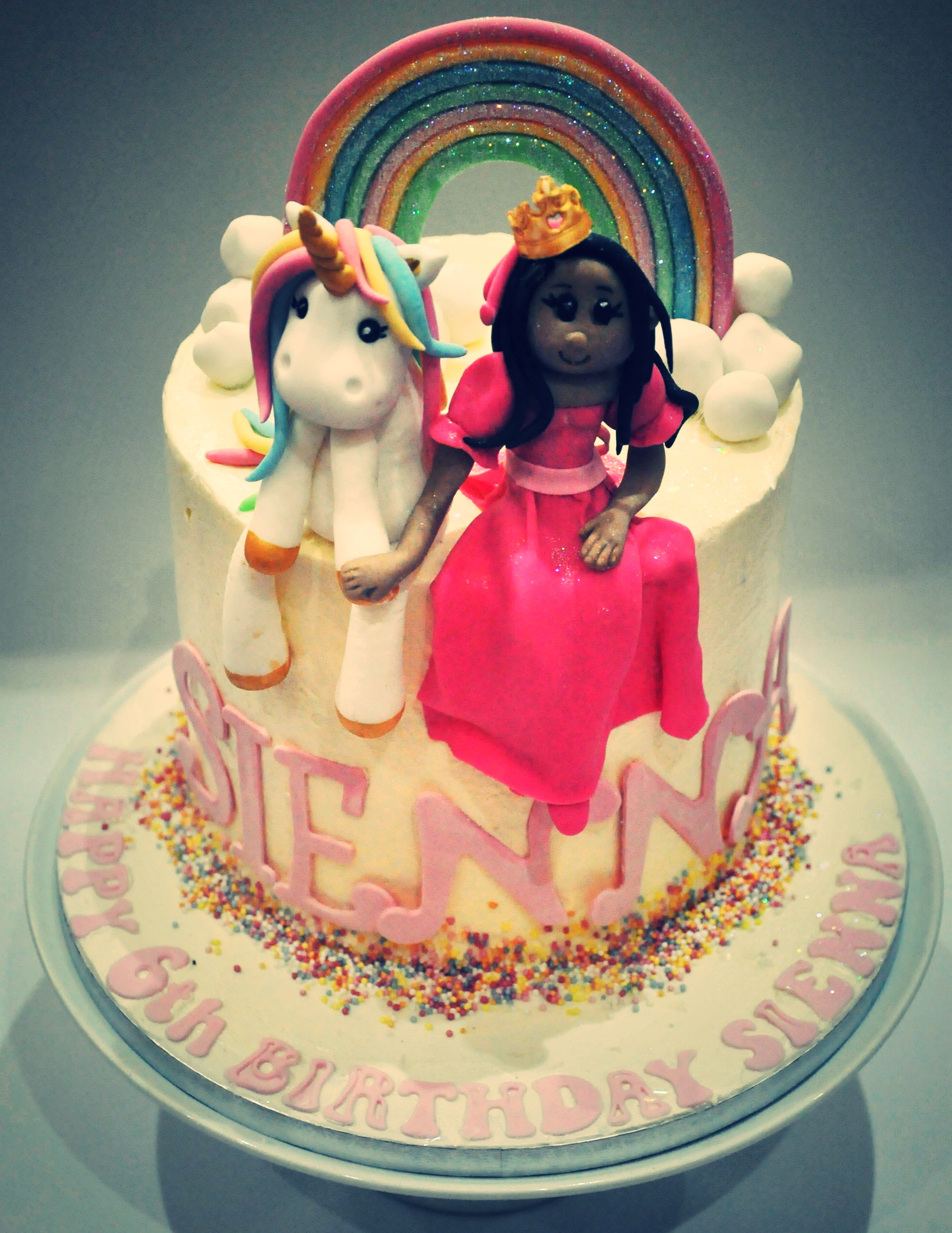 Princess and the unicorn - Here is a fun and sparkly rainbow cake with handmade princess and unicorn figures inside pastel coloured rainbow cake, delicious in seven coloured layers.