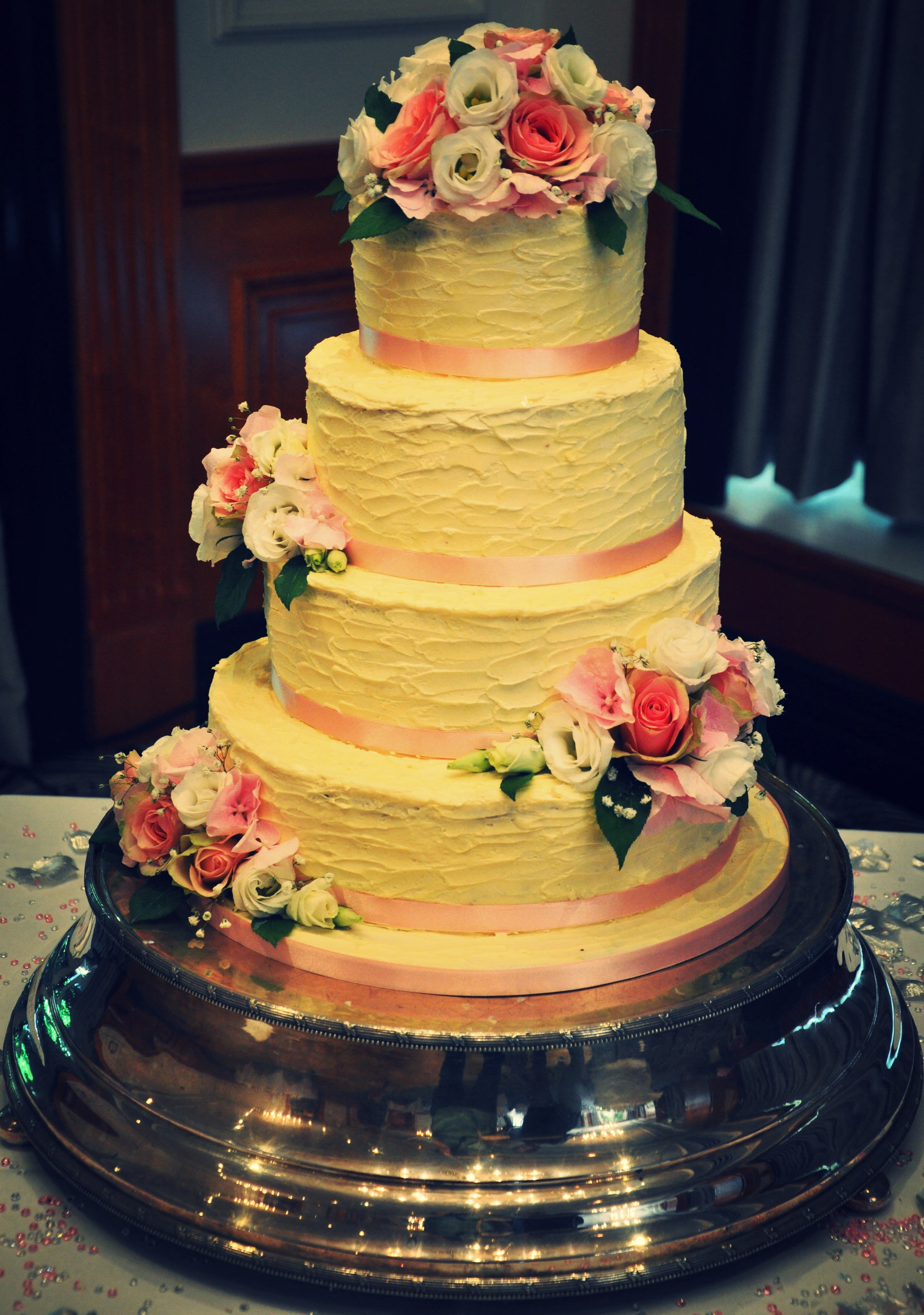 Four tier wedding cake - Beautiful four tier wedding cake in three layers with a stylish buttercream finish decorated with fresh flowers.