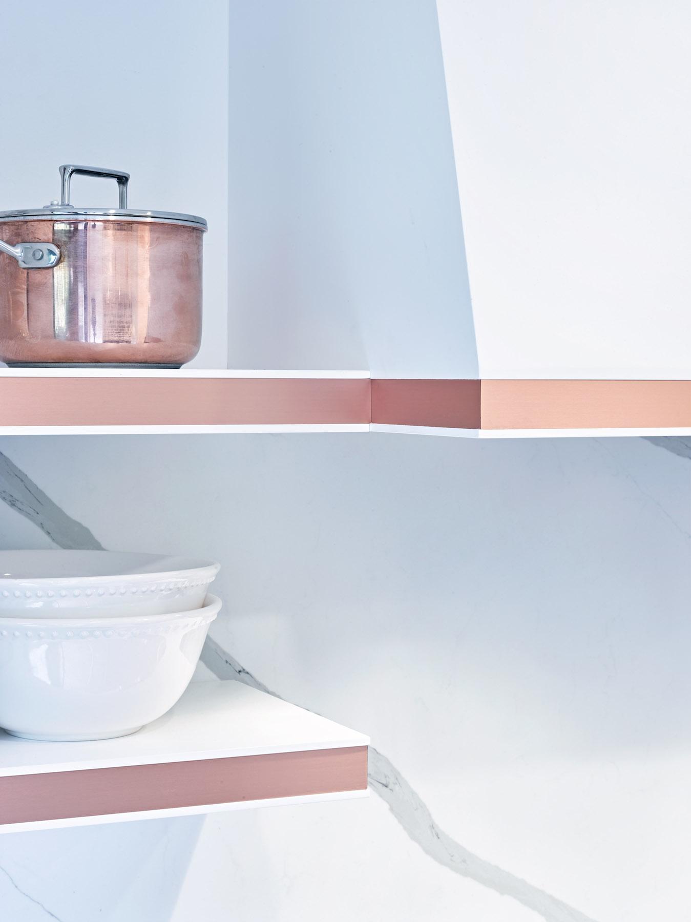White Quartz Backsplash and Furniture Hood with Brass Detail