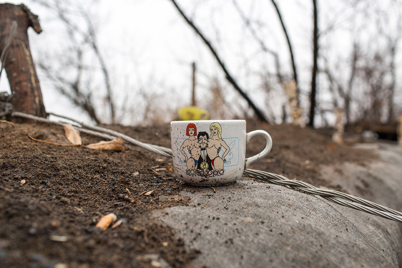 A Playboy coffee cup sits on the edge of trenches in Donetsk.