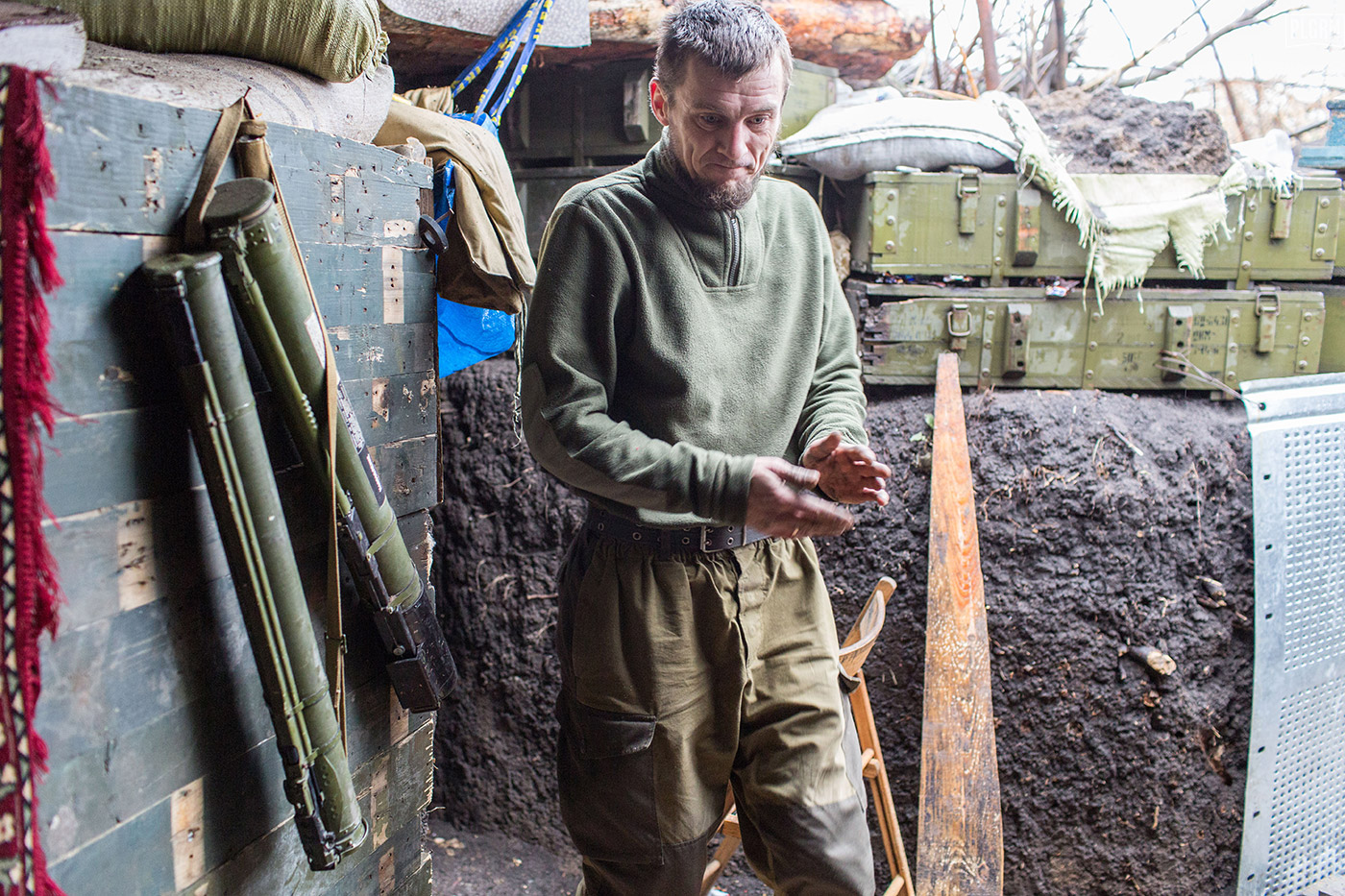 A Ukrainian soldier takes a break from constructing stairs to a sleeping area in one of the trench systems.