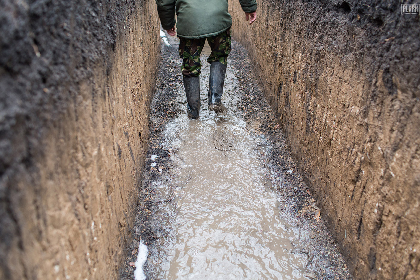 A Ukrainian soldier slogs through muddy, wet trenches as we walk along Ukrainian defensive positions on the front lines in Donetsk.