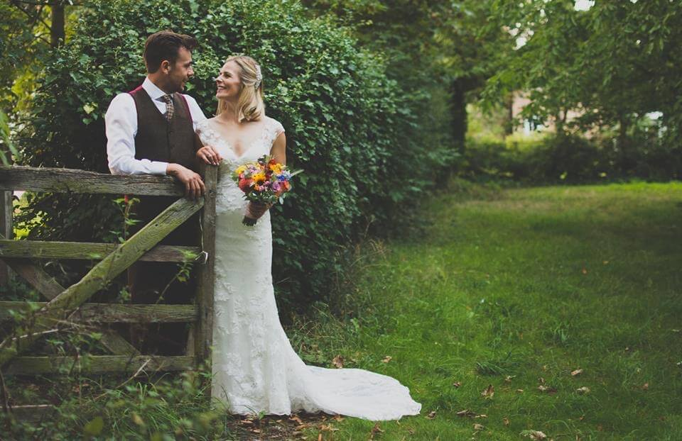 Hannah & Will Village country fete wedding in Cambridgeshire Couple at Gate Sunflower August Bouquet